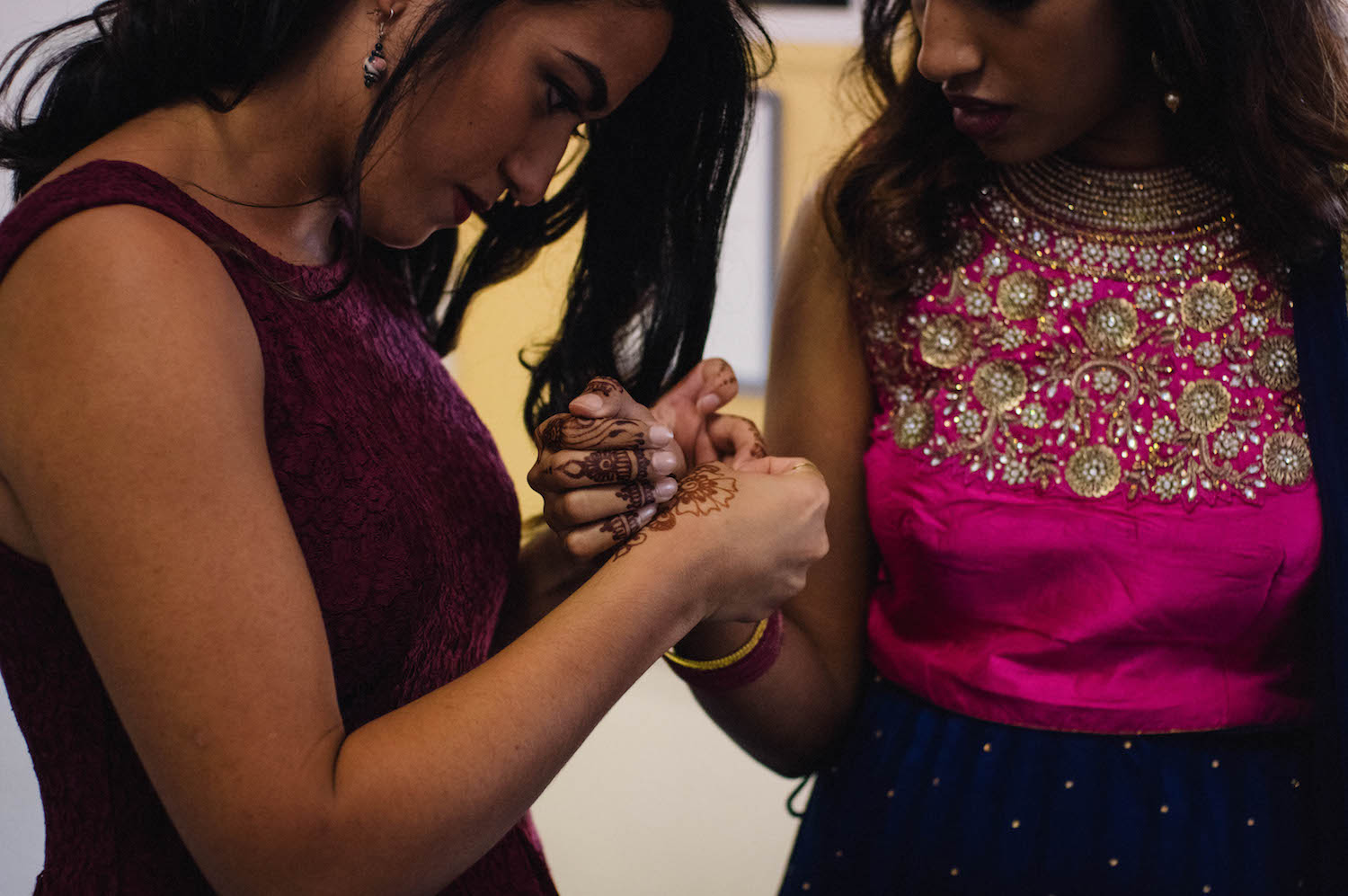 Bridesmaid helping the bride with her outfit change into her Indian dress taken by Rhianna May Destination Wedding Photographer.