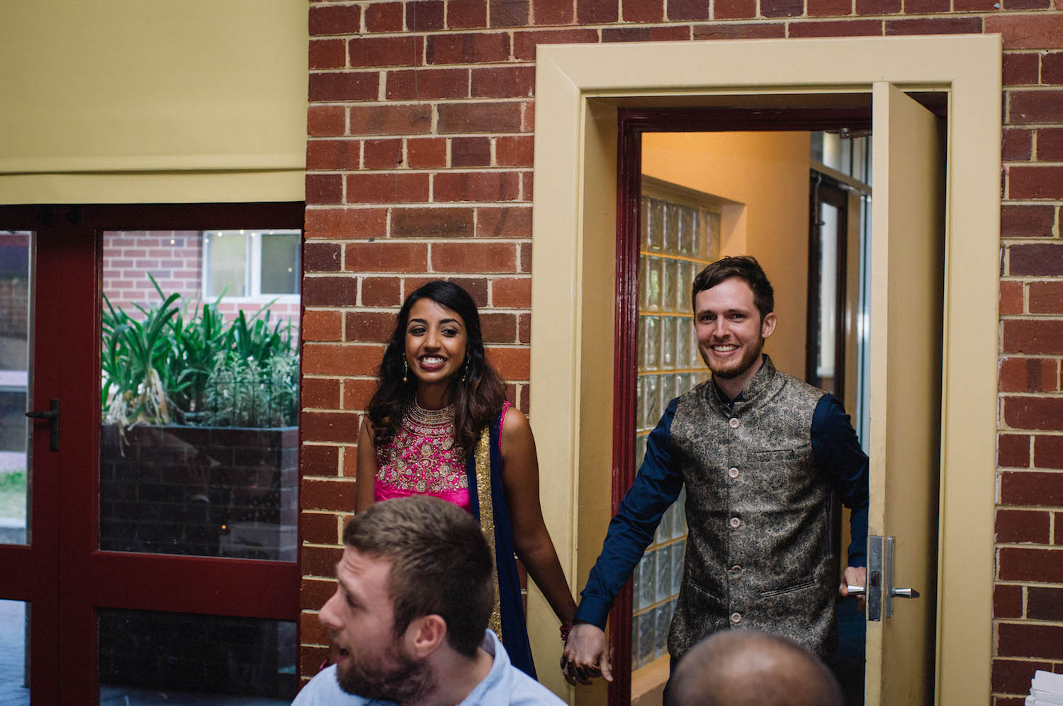 The bride & groom enter their reception at St Matthew's Anglican Church, Subiaco, wearing Indian wedding outfits.