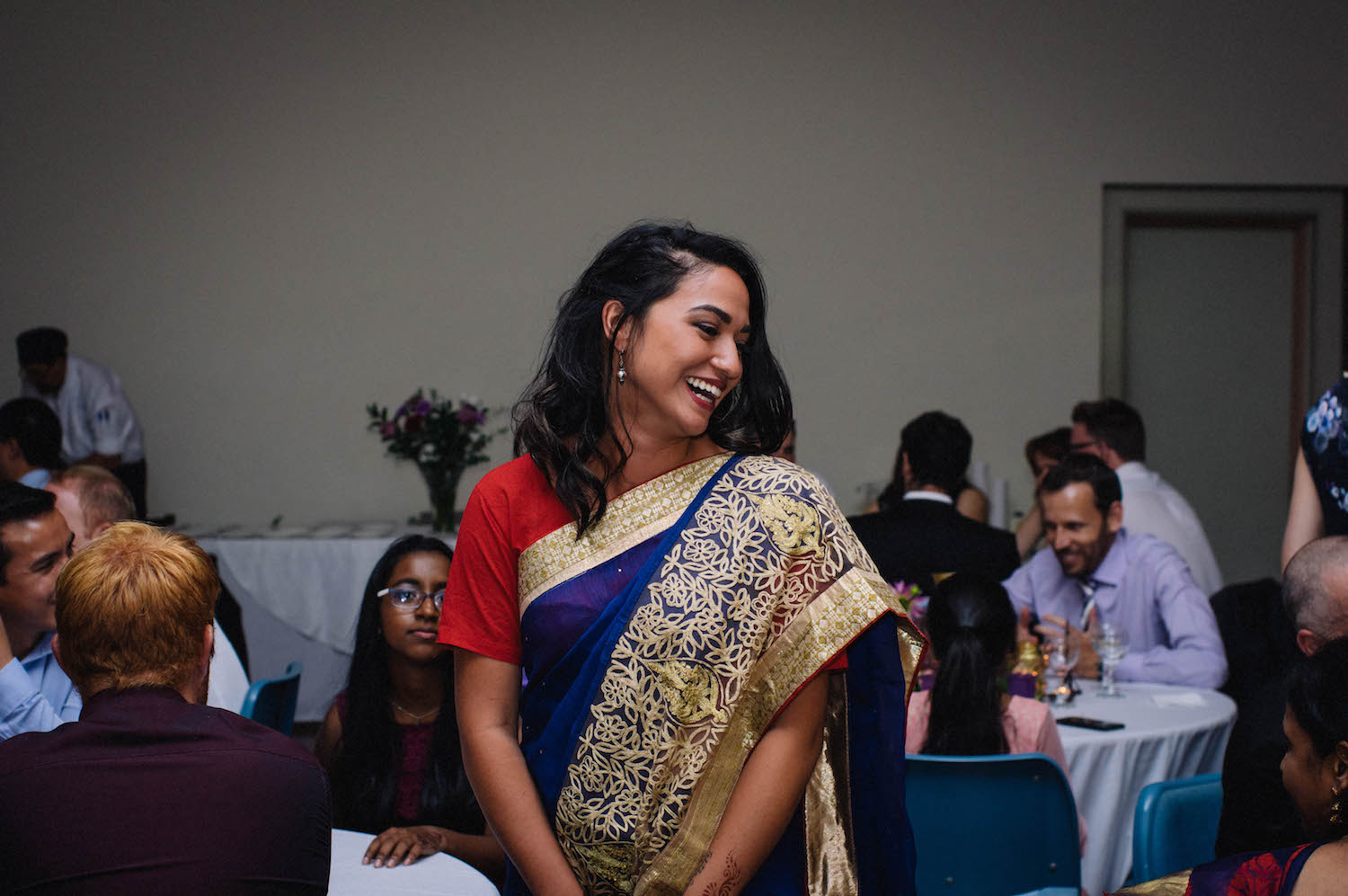 A candid wedding photograph of a bridesmaid in her Sari as she laughs with other guests