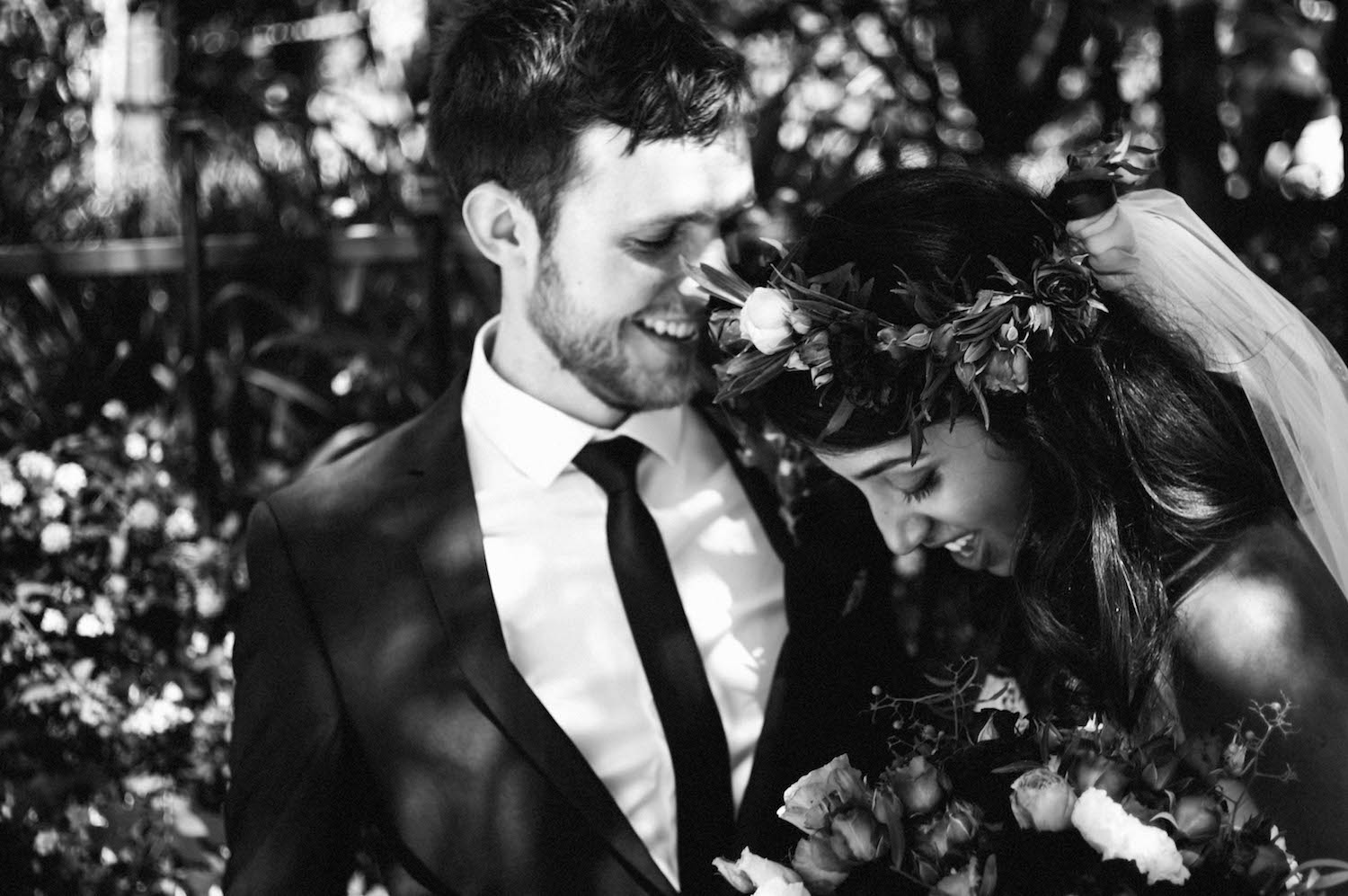A black & white photo of the bride & groom laugh together during their portrait session after their Subiaco wedding.