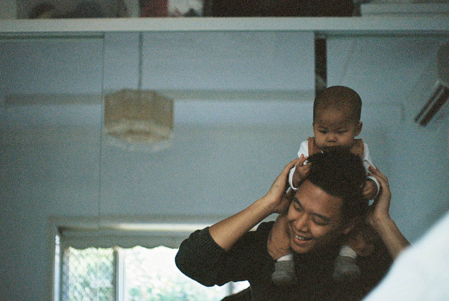 Baby Alexa & her Dad playing at home, photographed on 35mm film in Wembley.