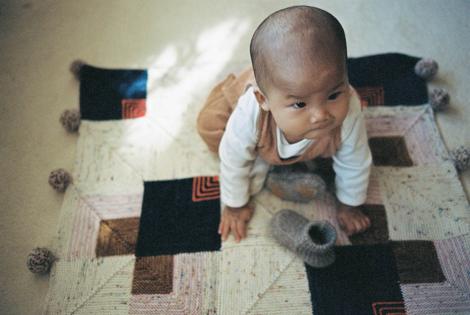 A mix of dappled light, baby Alexa and her missing woollen slipper captured on 35mm film.