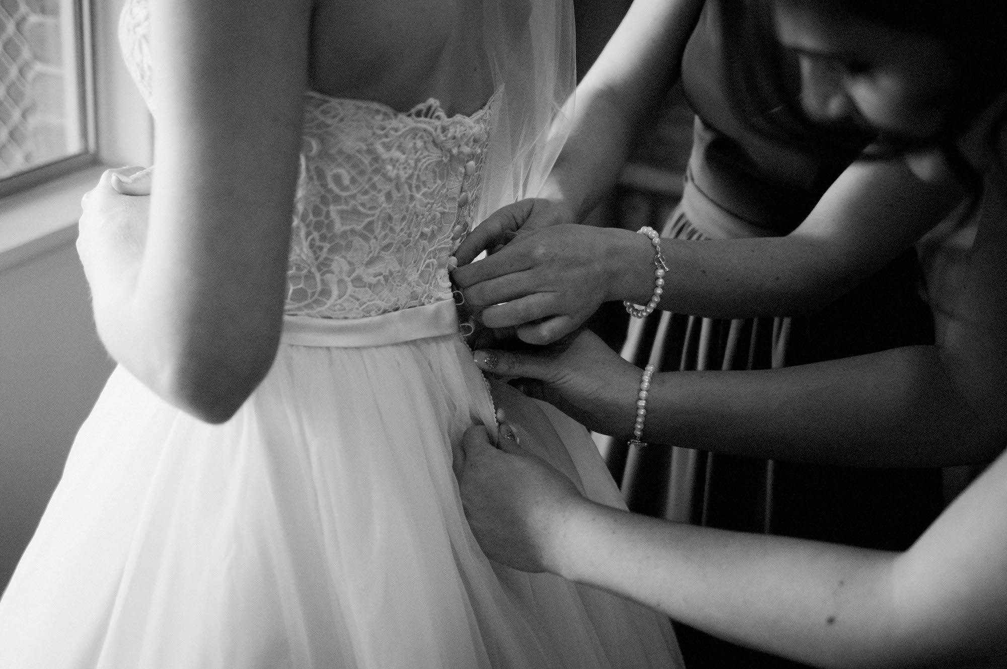 The bridesmaid's helping button up the bride's dress.