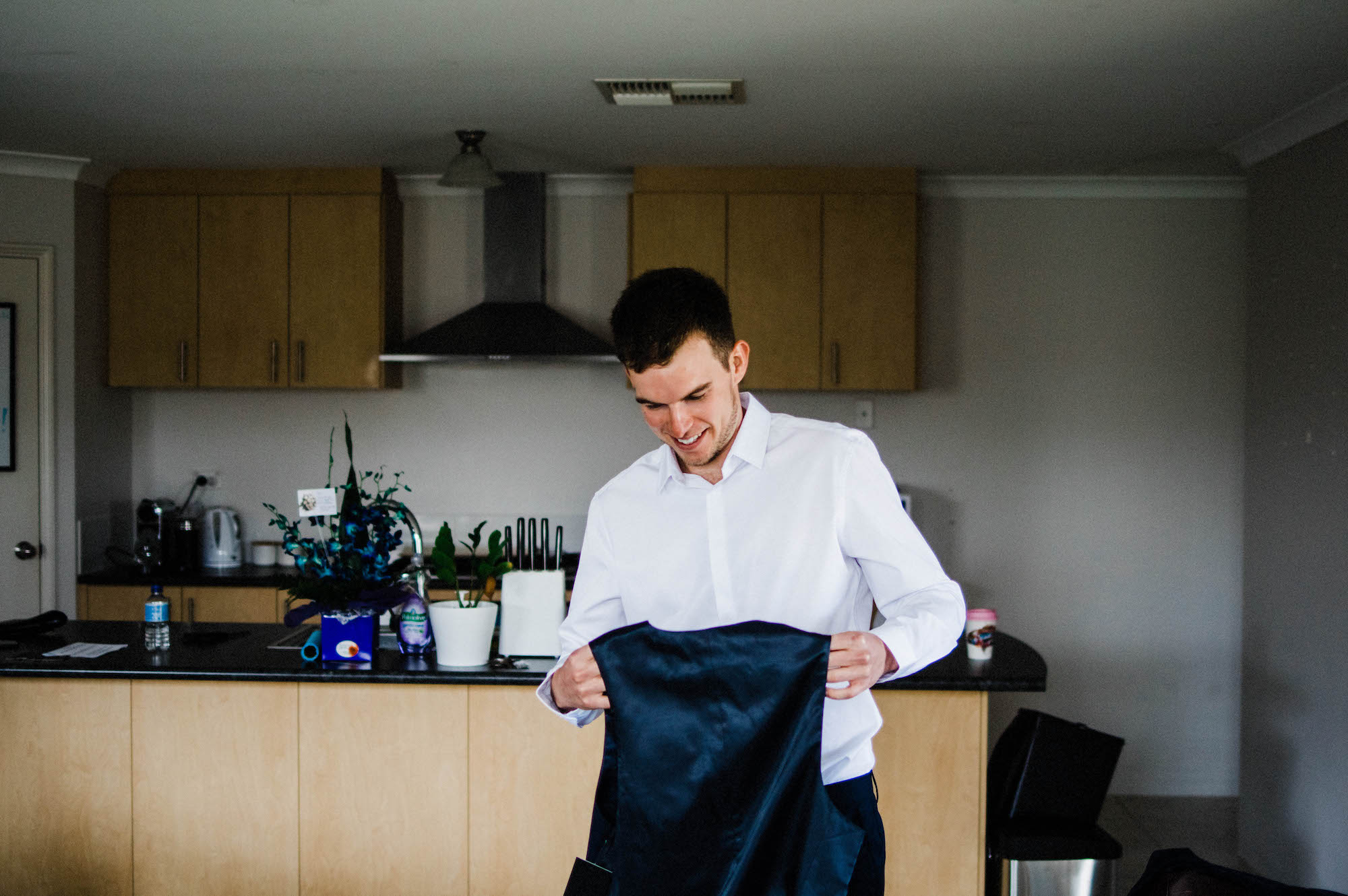 The groom getting his vest ready to wear before his wedding.