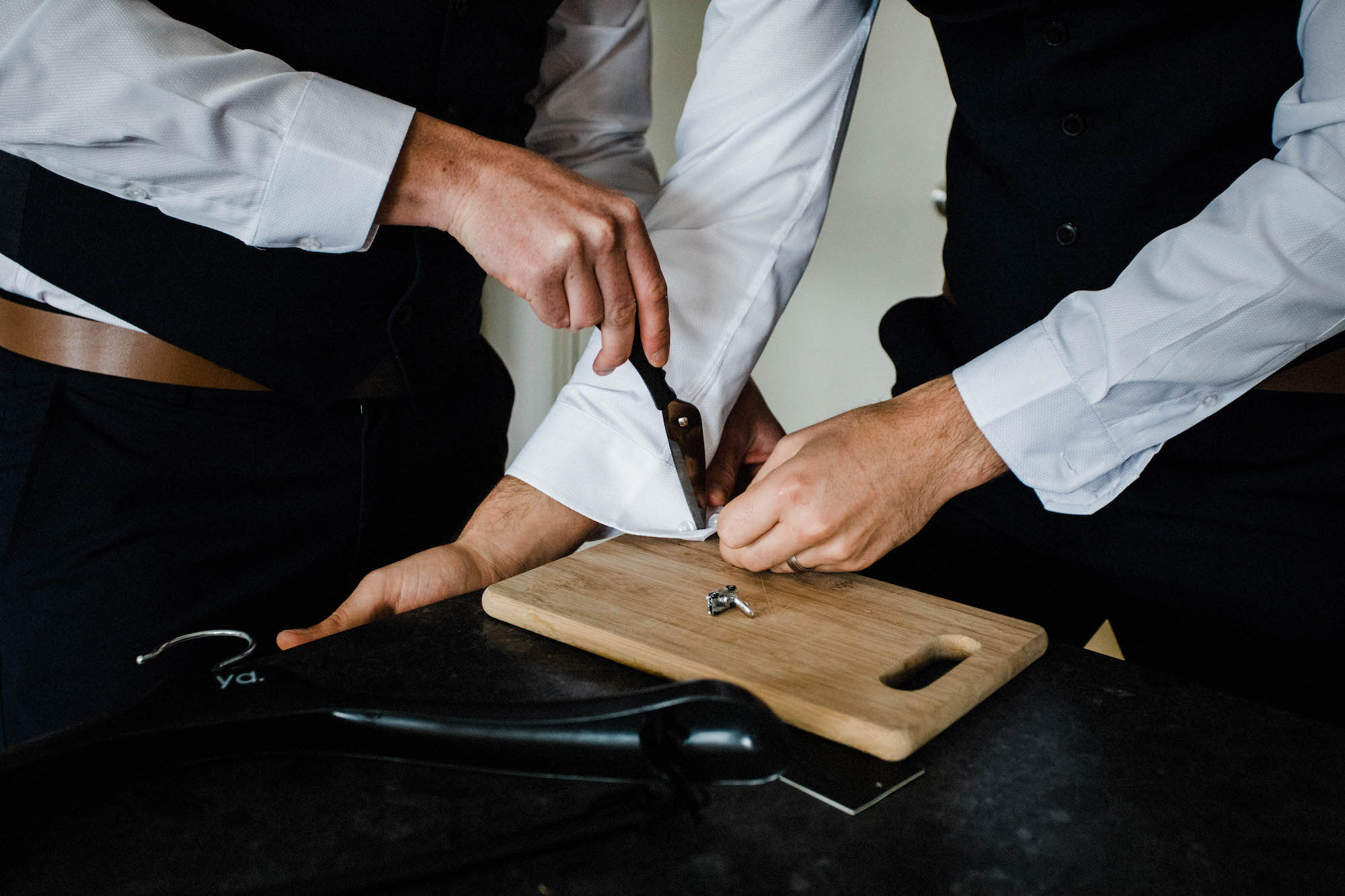 A photo of groomsmen creating French cuffs using a knife.