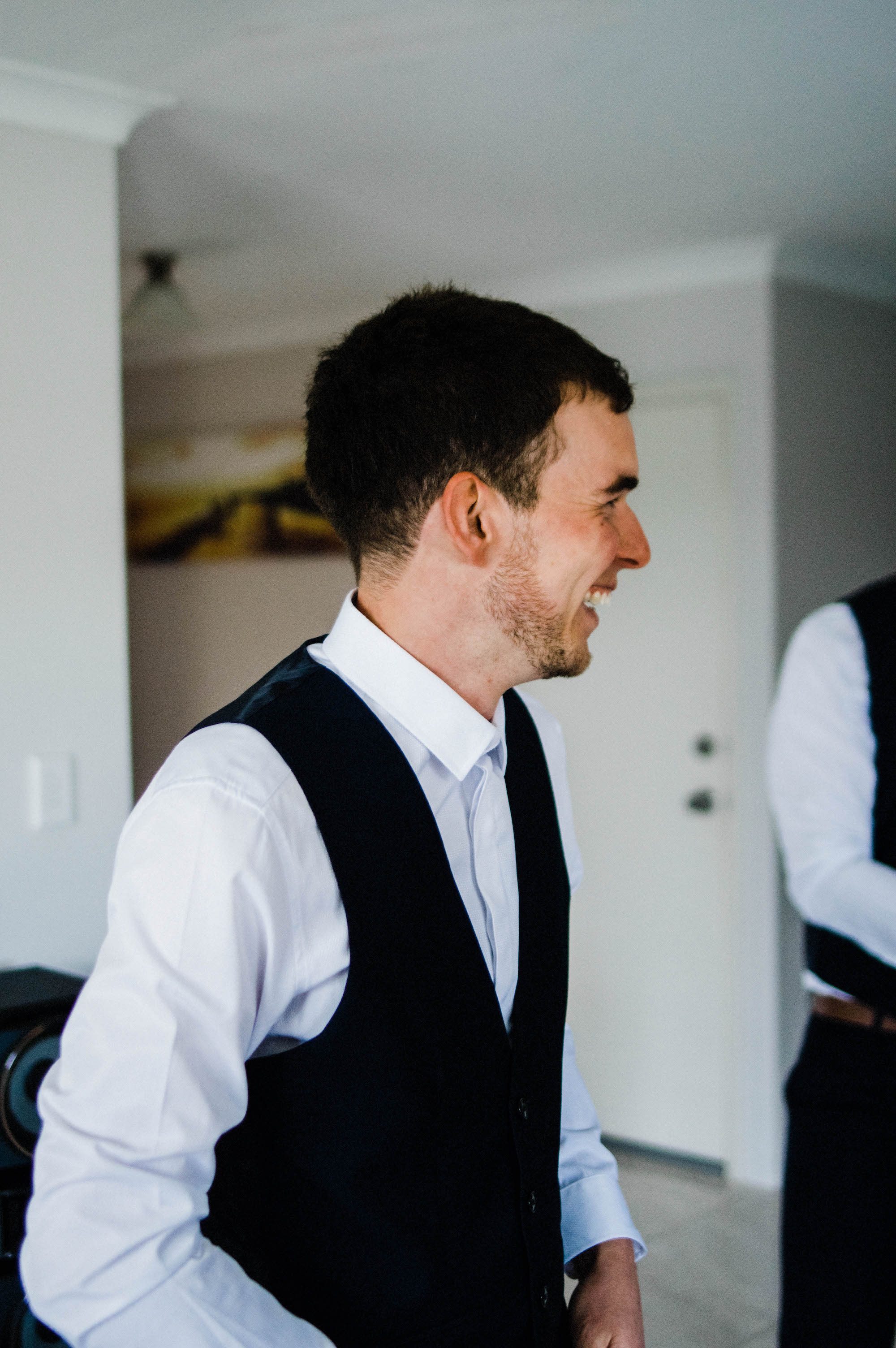 A photo of the groom smiling while getting ready for his Perth wedding.