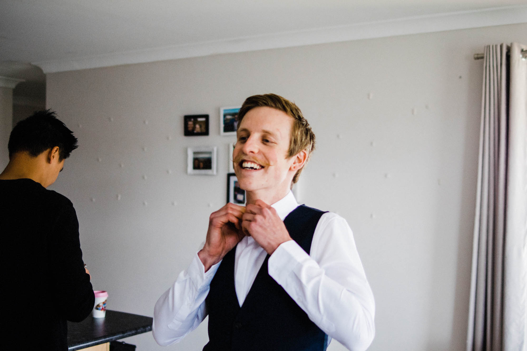 A groomsmen doing his bowtie the morning of a Perth wedding.
