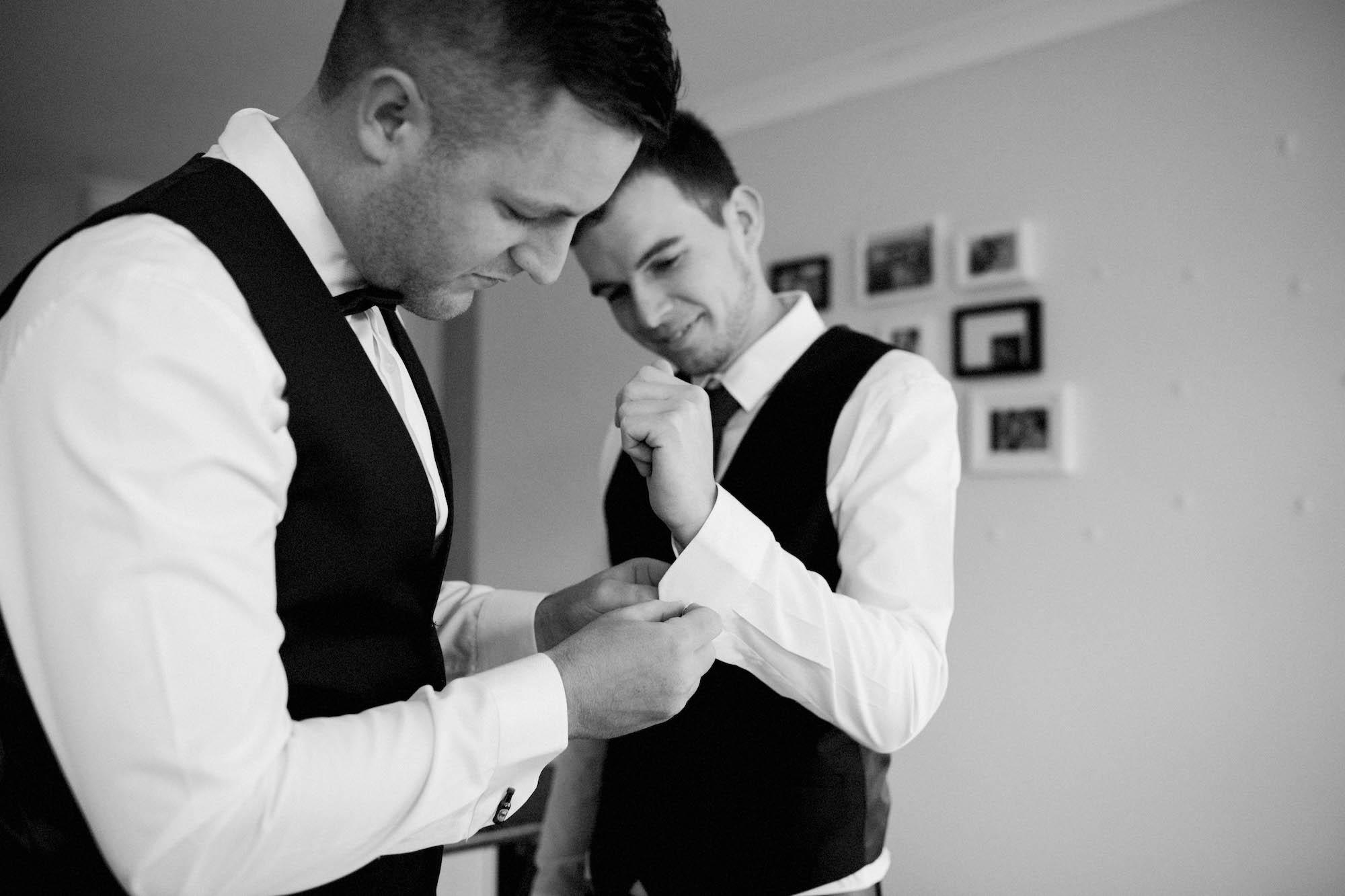 Groomsmen helping the groom put his cufflinks on before his Perth wedding.