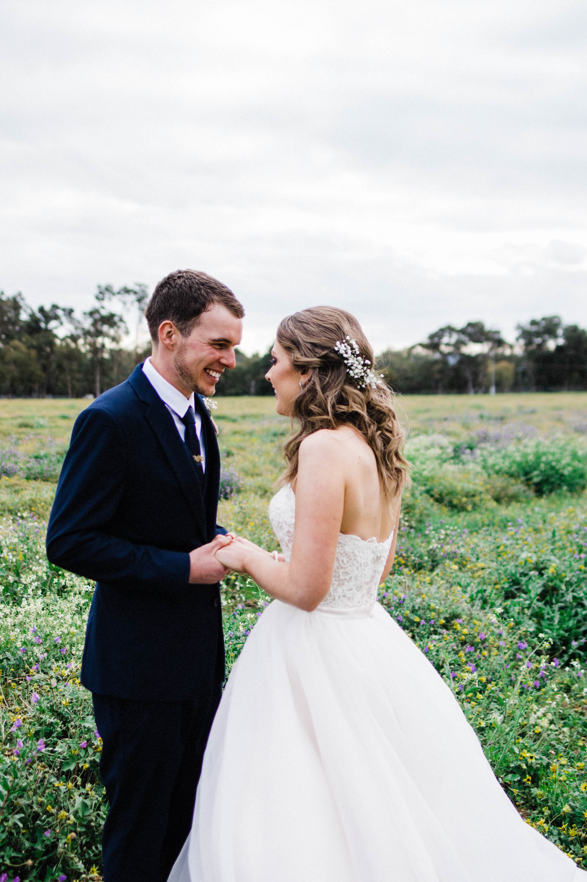 Natural wedding photography of the bride & groom laughing together in a field of spring flowers in Australia's countryside.