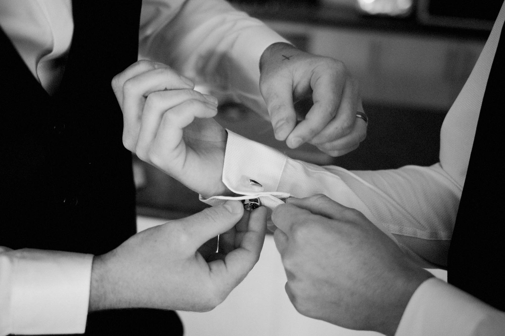 A detail of the groomsmen helping the groom with his cufflinks.
