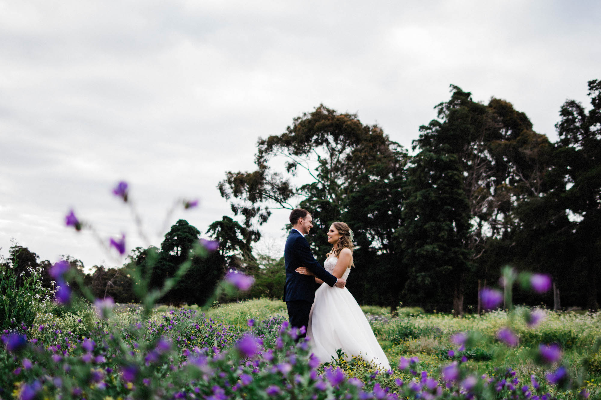 The bride & groom share a moment in a field of flowers at Quarry Farm during their Spring wedding.