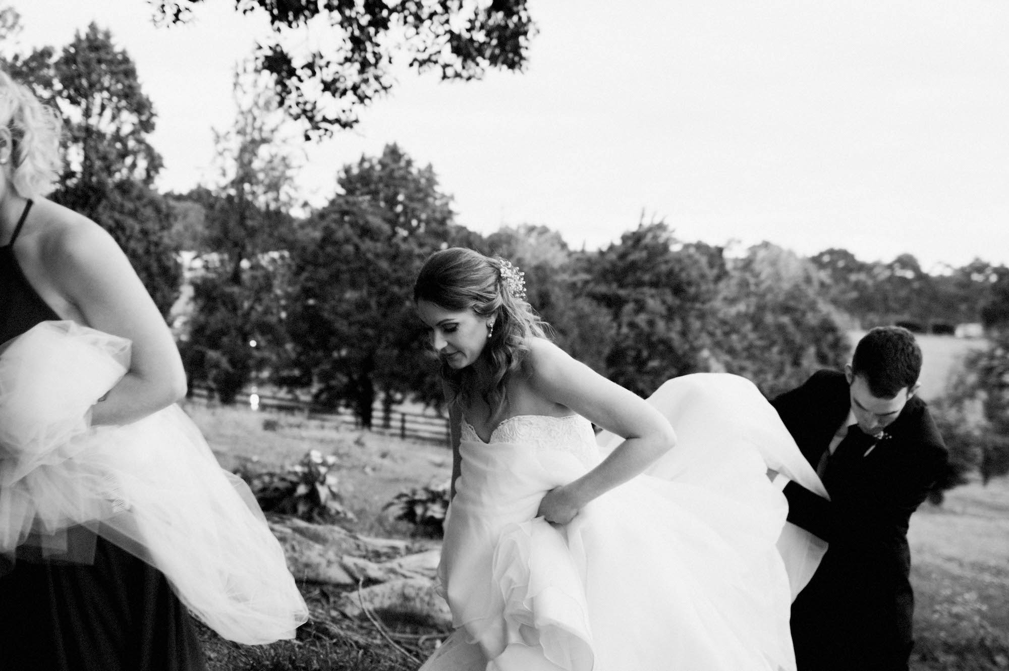 Candid black & white wedding photography of the bride & groom walking together in Australia.
