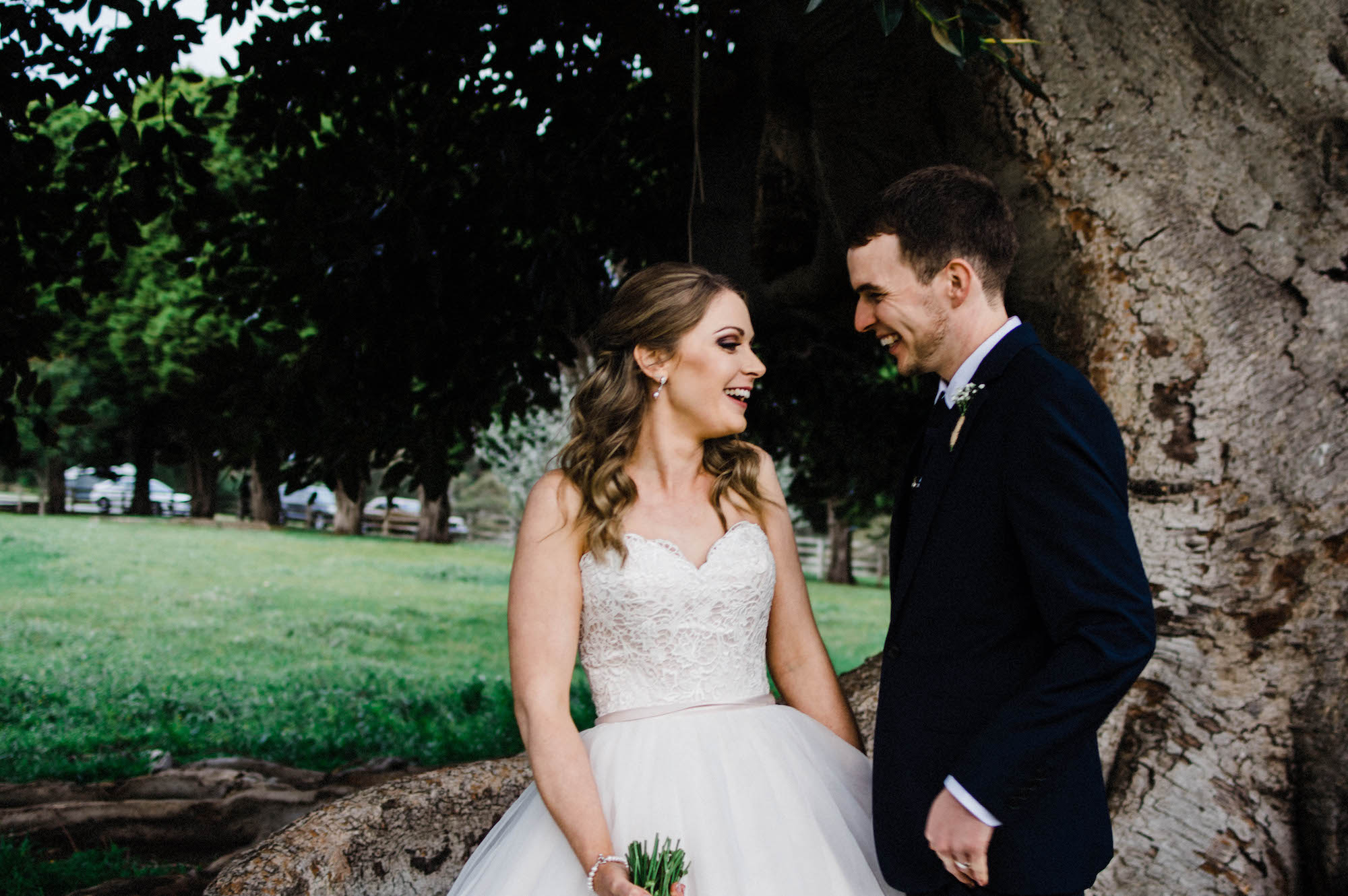 A candid wedding photo of the bride & groom laughing together.
