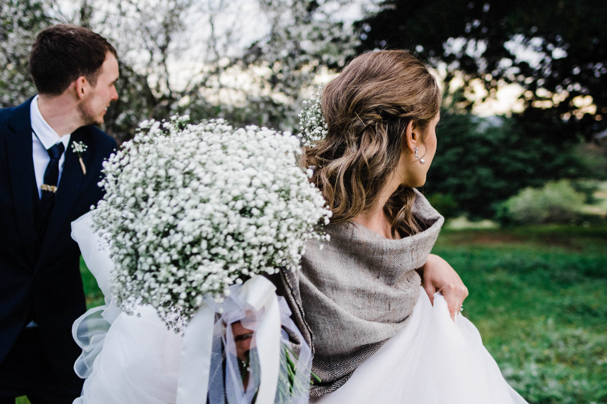 A candid wedding photo of the bride & groom walking together.