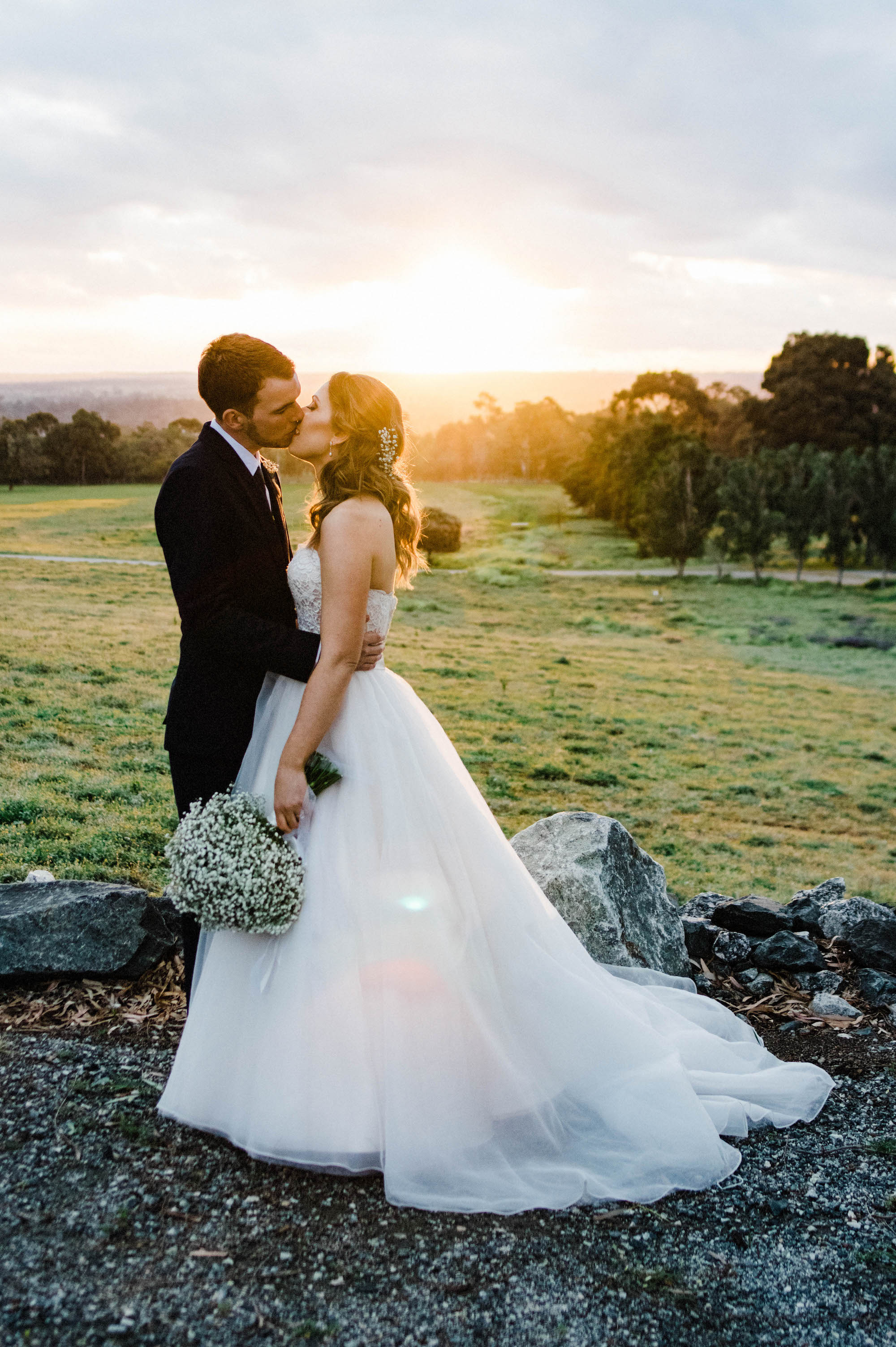 Portrait wedding photography of the bride & groom kissing in front of an incredible September sunset.