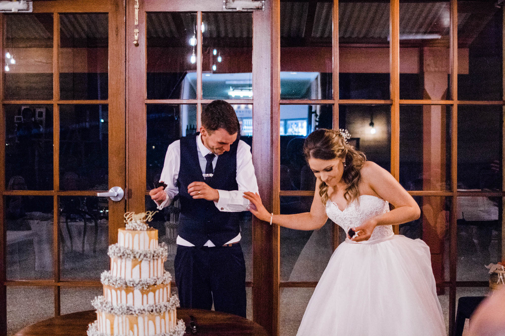 The bride & groom laugh after feeding each other cake at their Quarry Farm wedding.