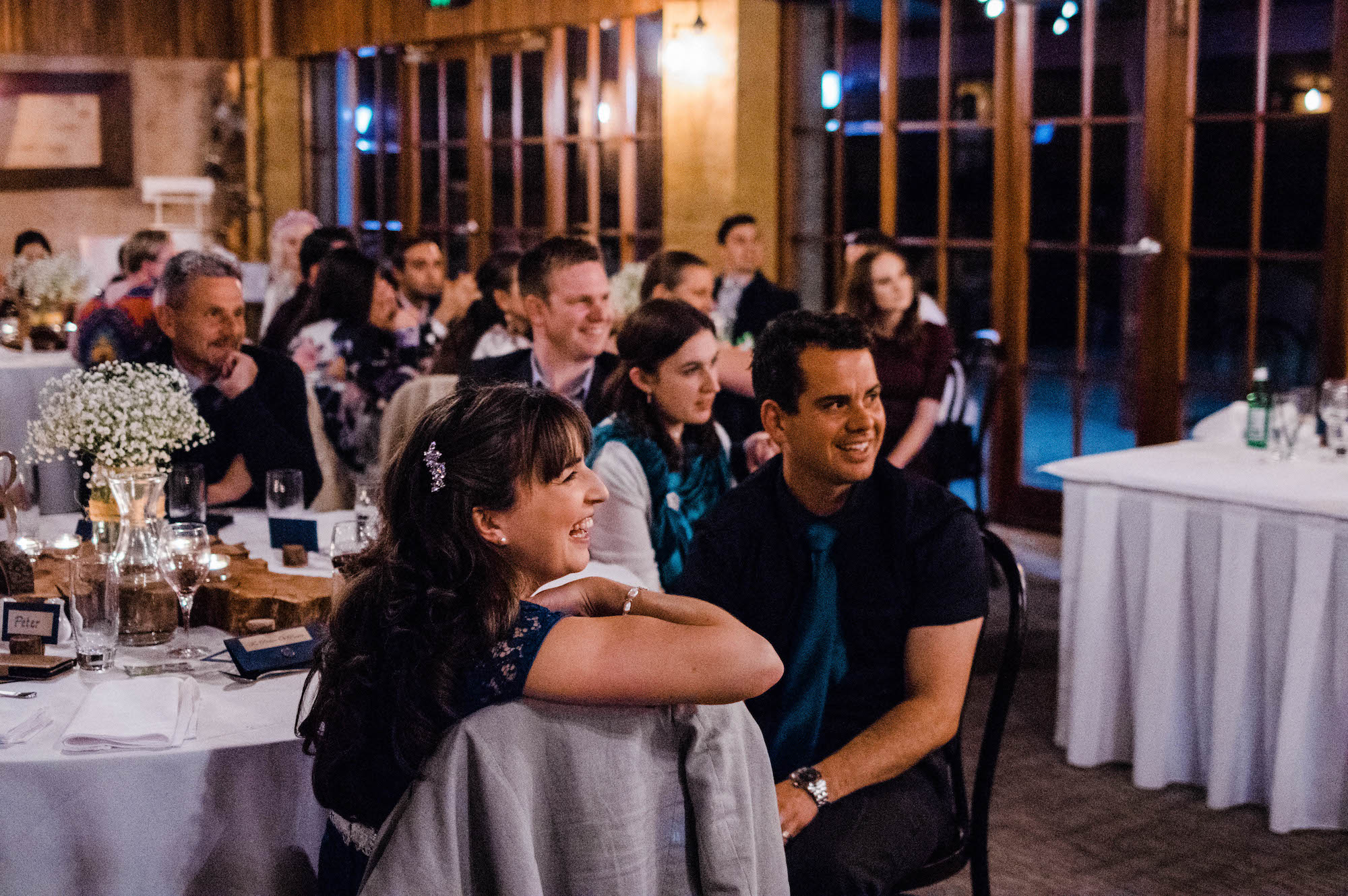 Guests laugh together during speeches at a Quarry Farm wedding.