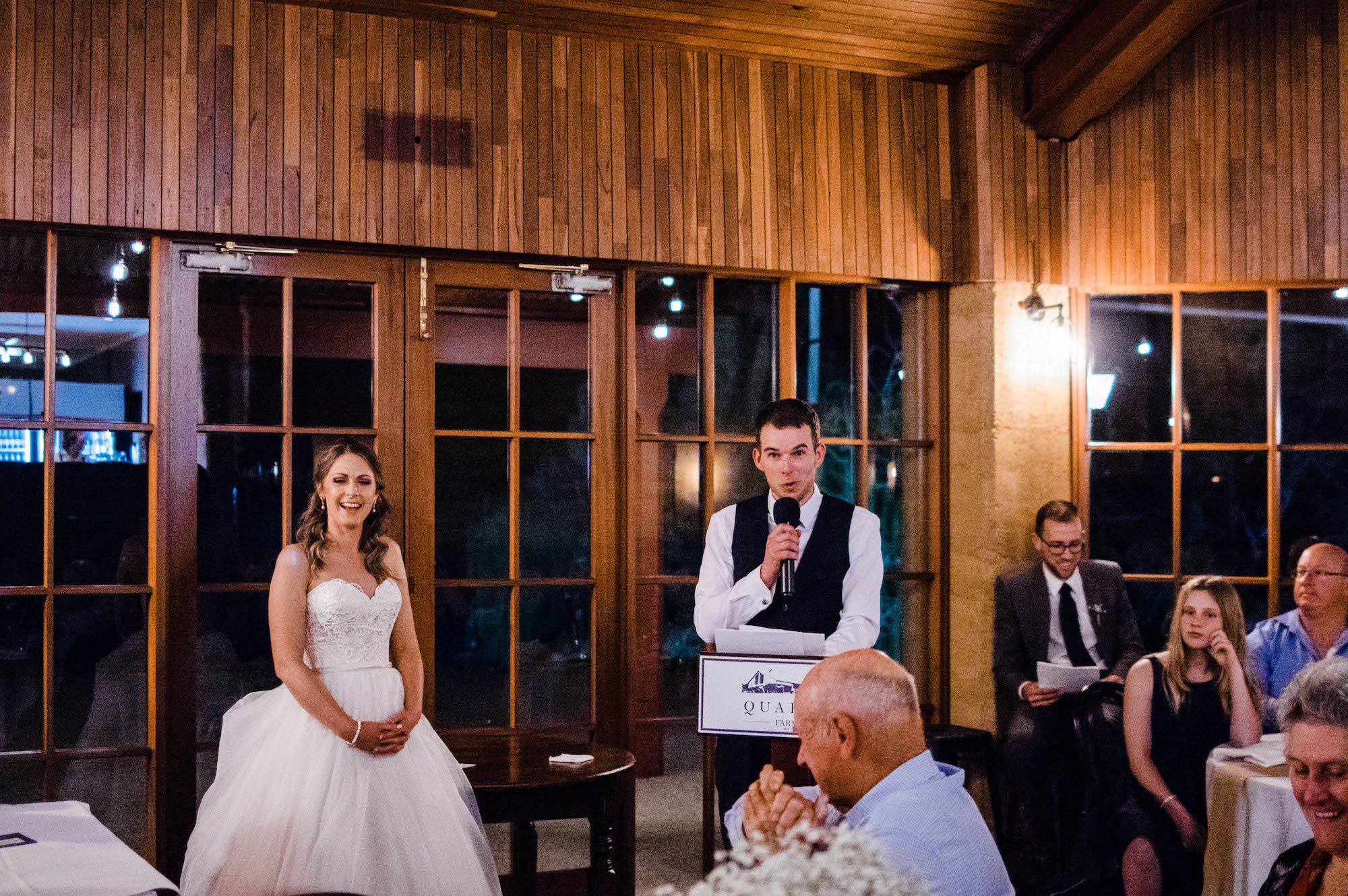 The bride laughs during the grooms speech at their wedding reception.
