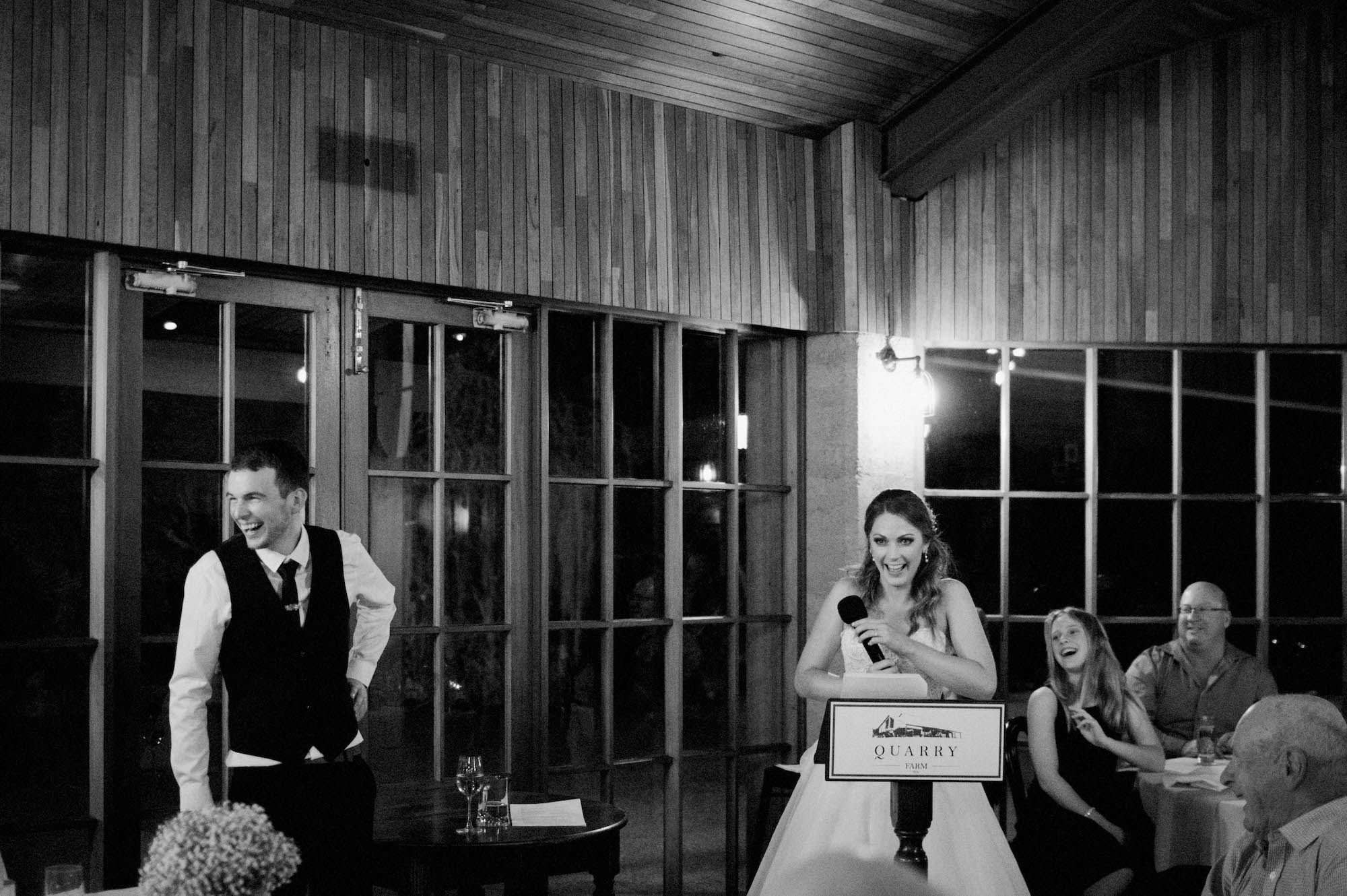 A black & white wedding photo of the bride & groom laughing during the bride's speech at their Byford wedding.