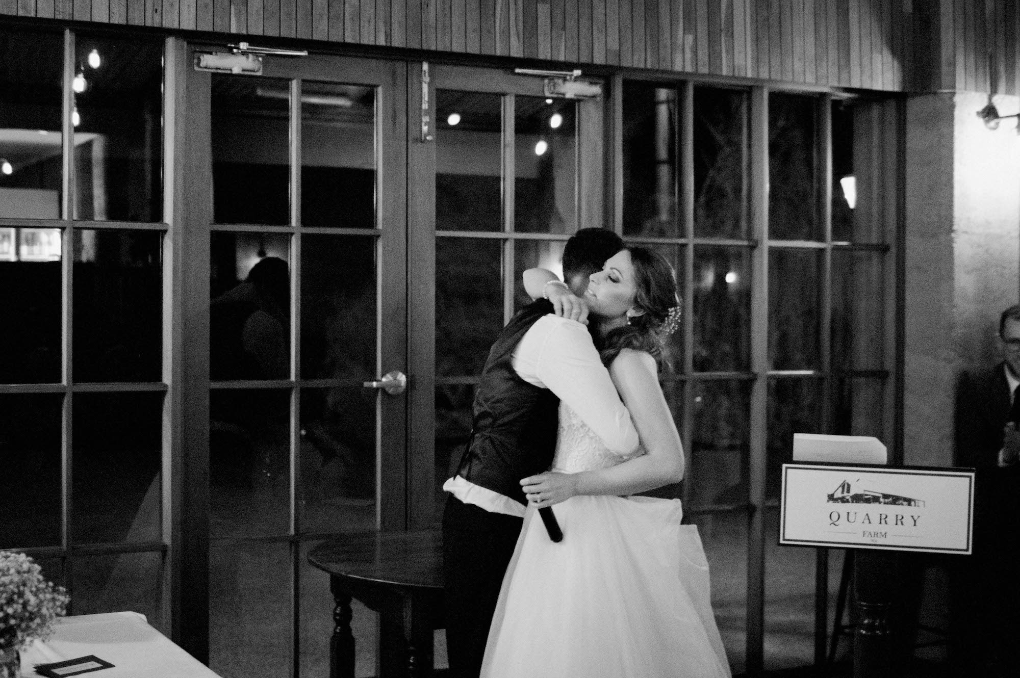 A black & white wedding photo of the bride & groom hugging after their speeches.