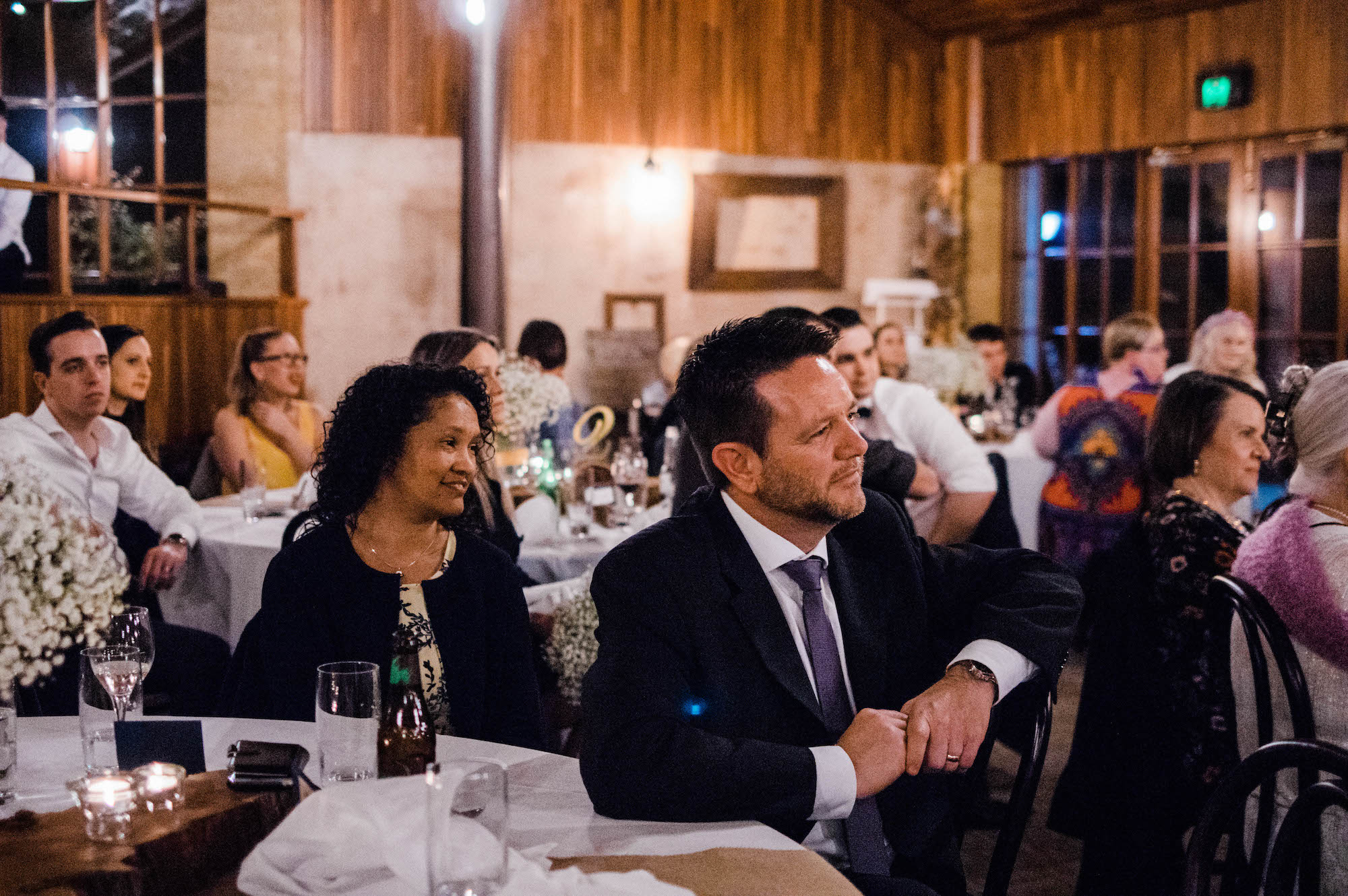 Guests smile during the bride & groom's speech at their Perth wedding.
