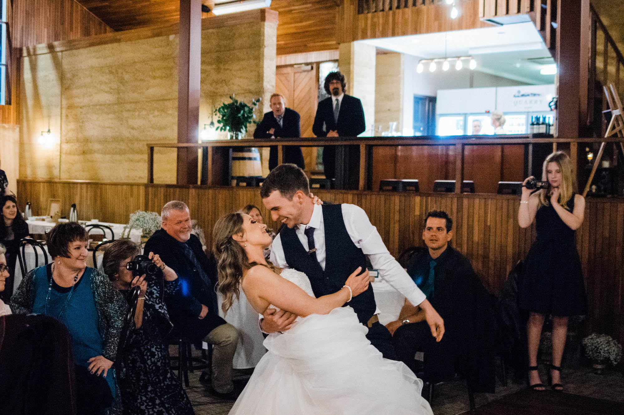 A wedding photo of the groom dipping his bride during their first dance.