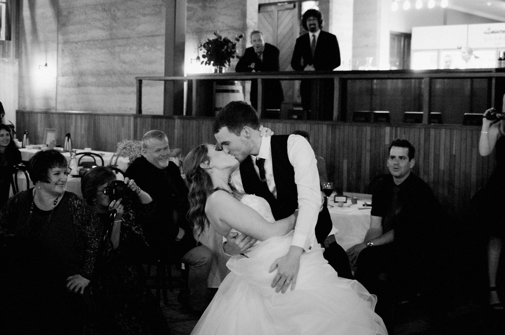 A black & white wedding photo of the groom kissing his bride during their first dance.