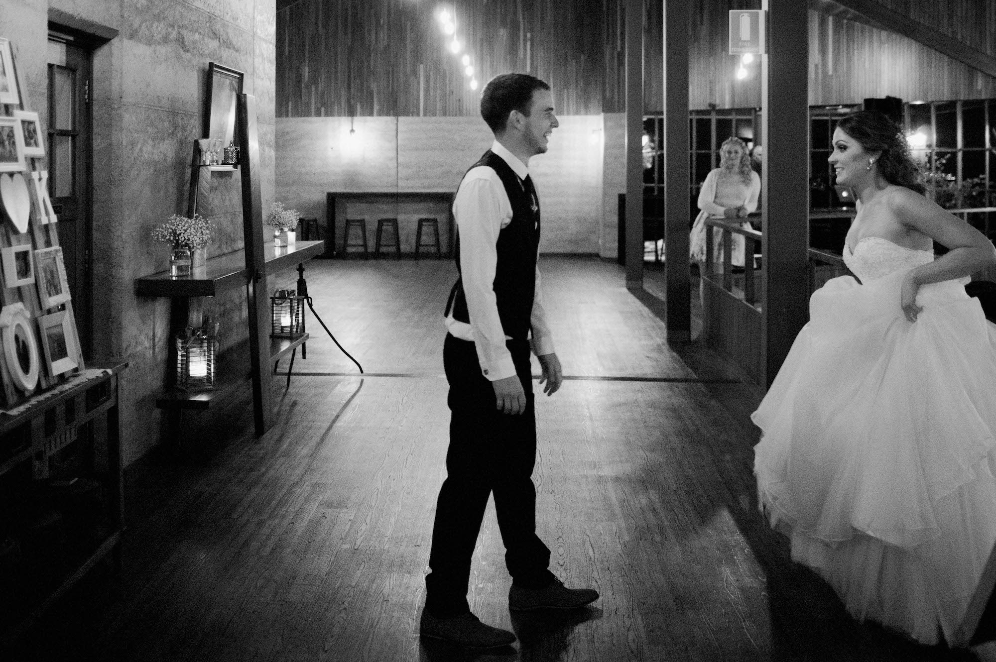 A black & white photo of the bride getting ready for a lift in her first dance at Quarry Farm.