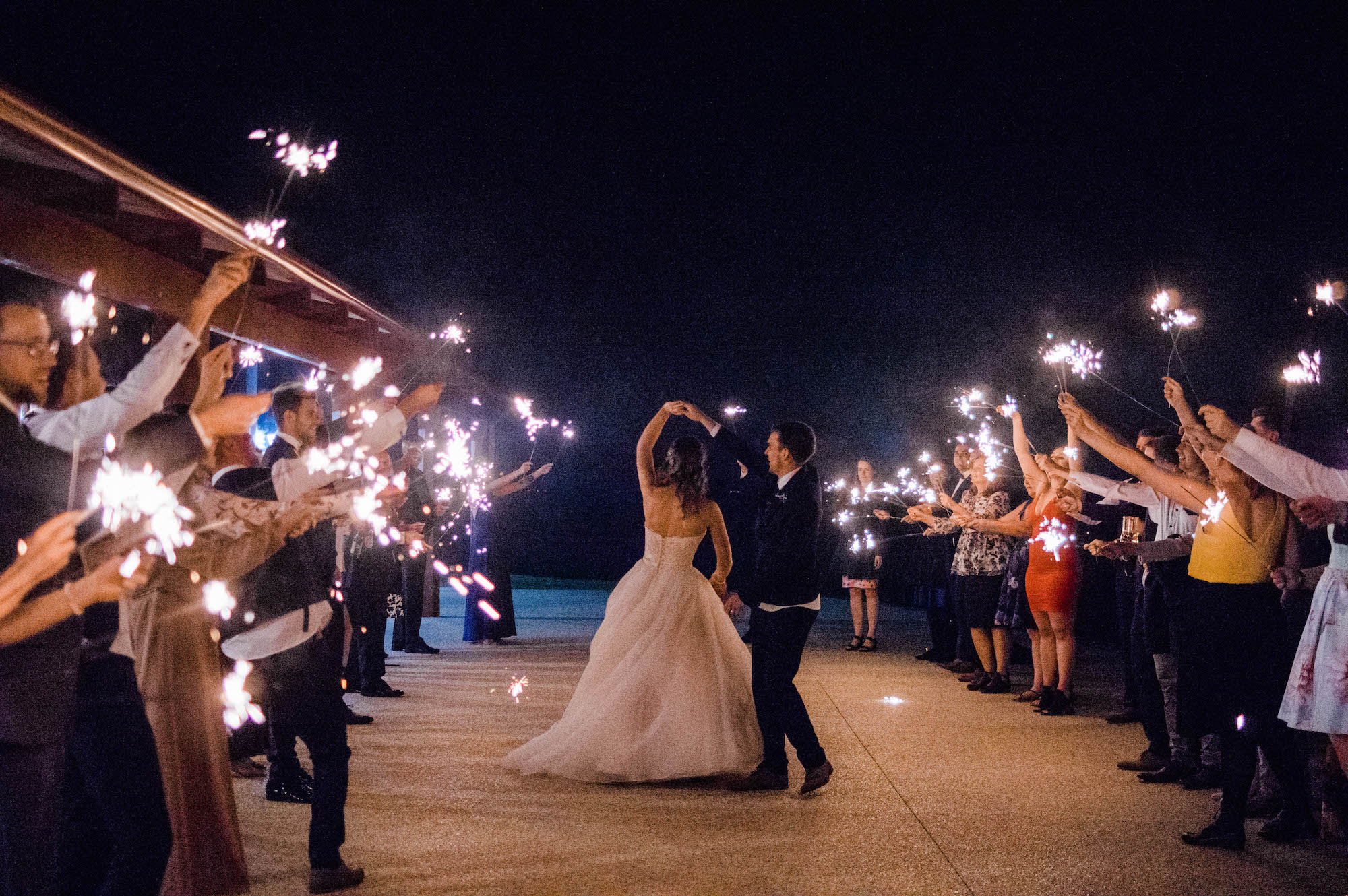 The groom dances with the bride as they do a sparkler exit at Quarry Farm, Australia.