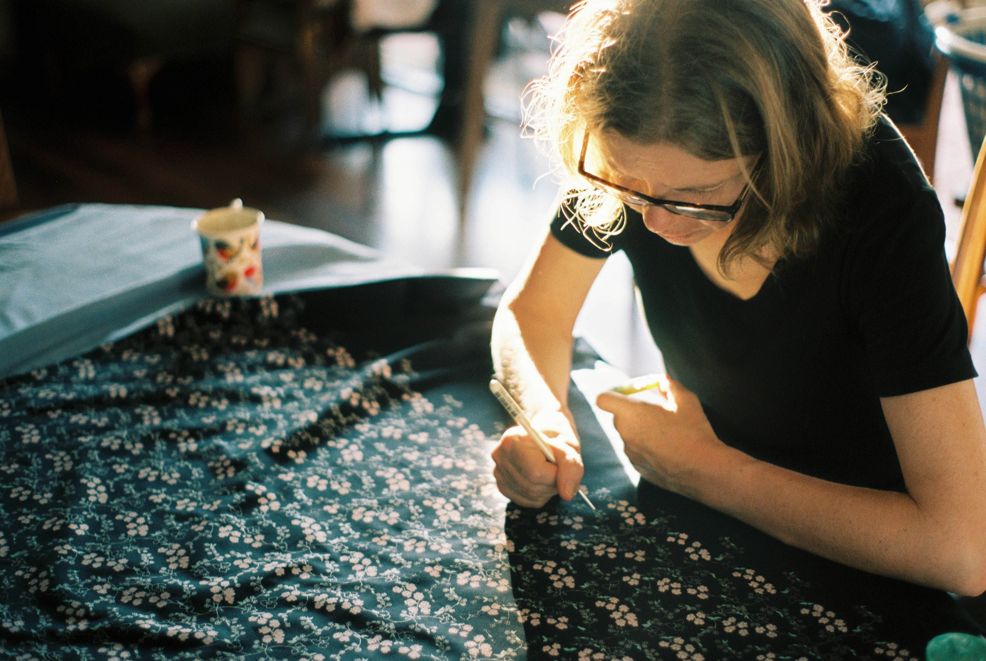 A photo of the Mother-of-the-Groom hand-painting fabric for bowties taken by Rhianna May Destination Wedding Photography