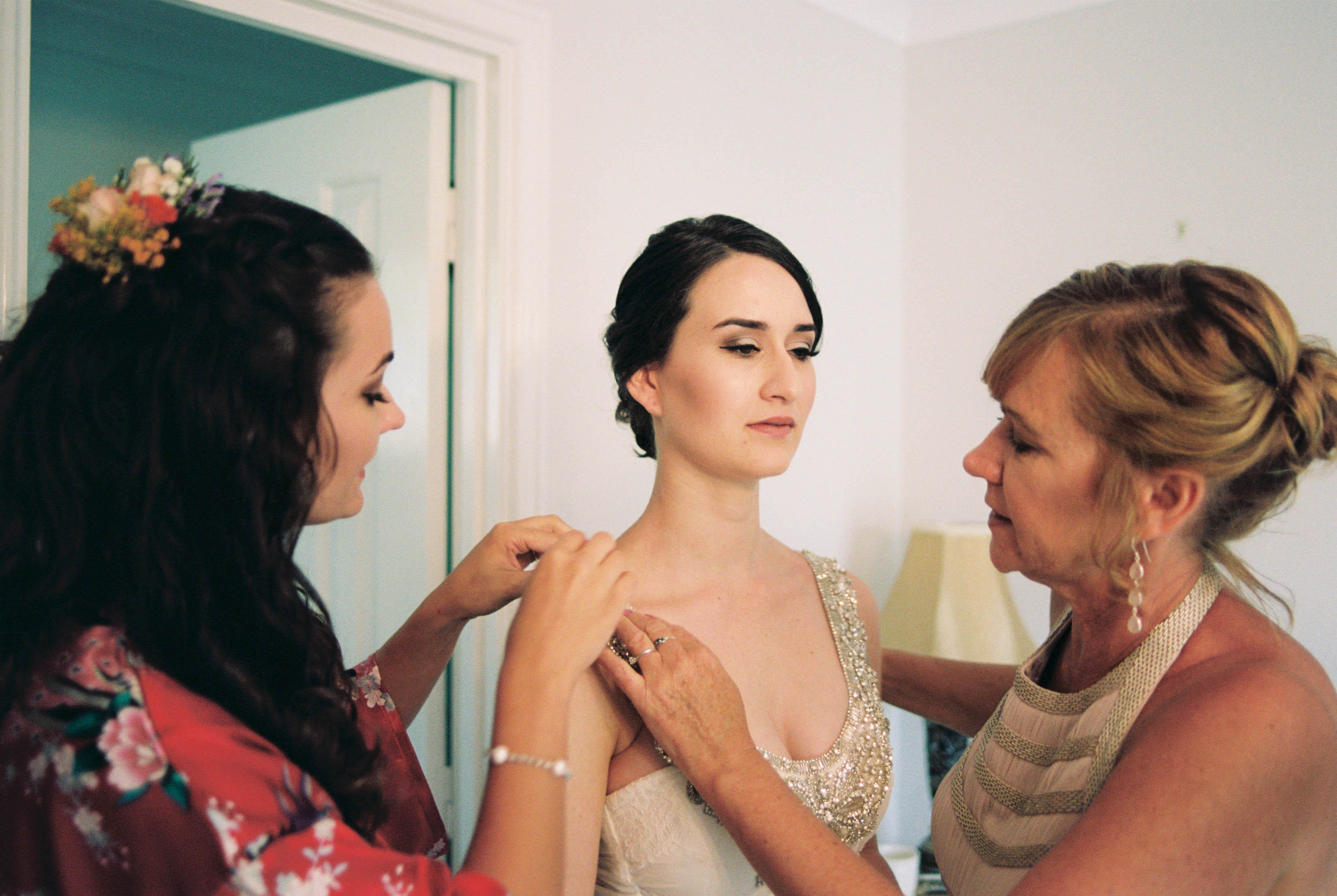 A photo of the bride's Mum and Maid of Honour helping her with her dress before her Destination Wedding in the South West