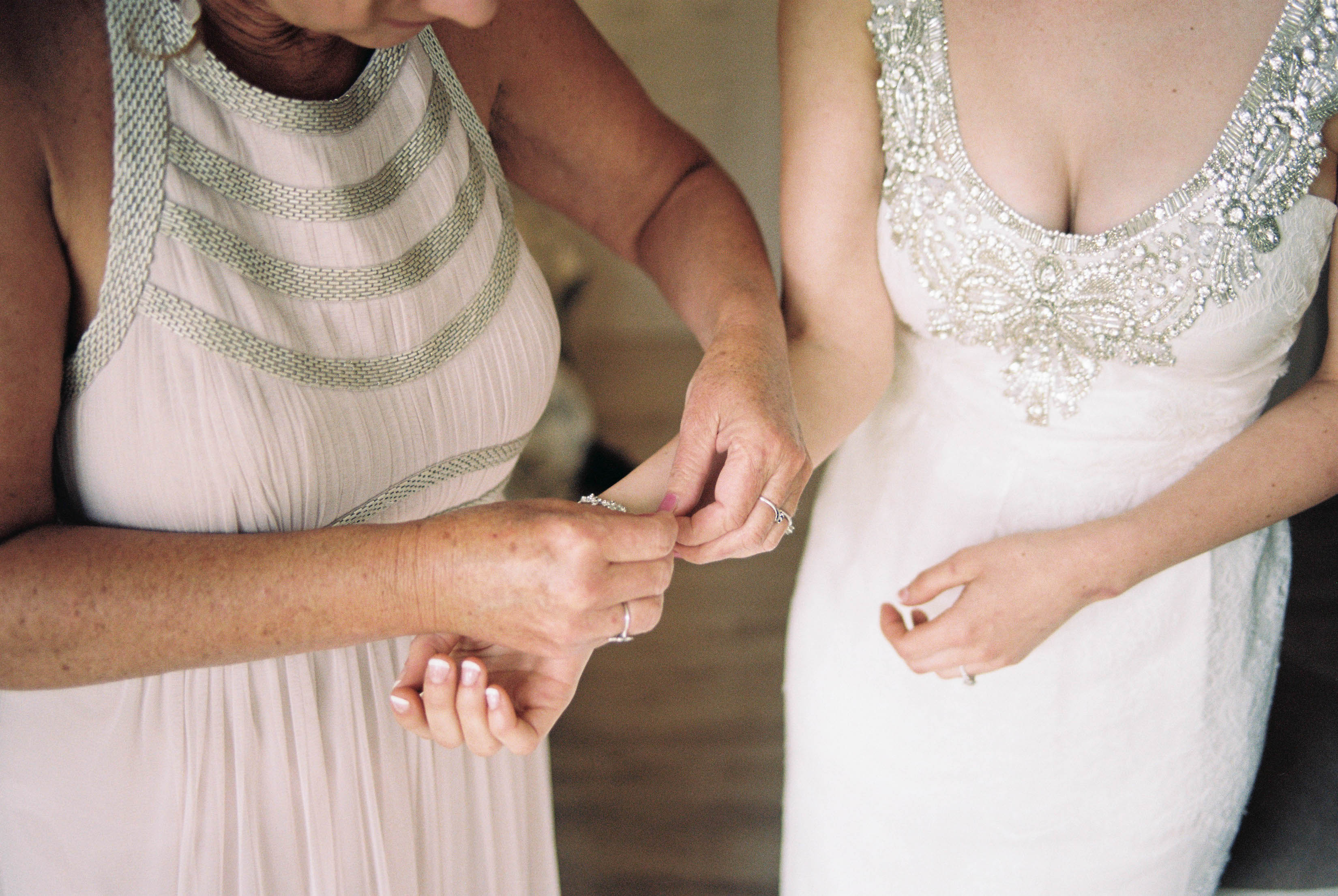 A film photo of the bride's Mum helping her put her bracelet on
