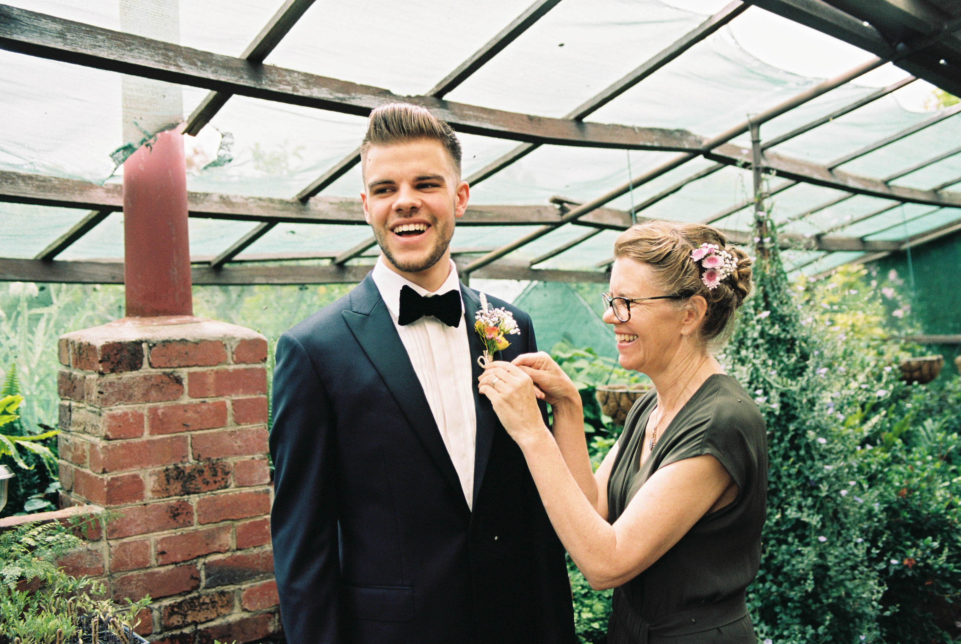 A 35mm wedding photo of a groom's Mum helping him put his buttonhole on