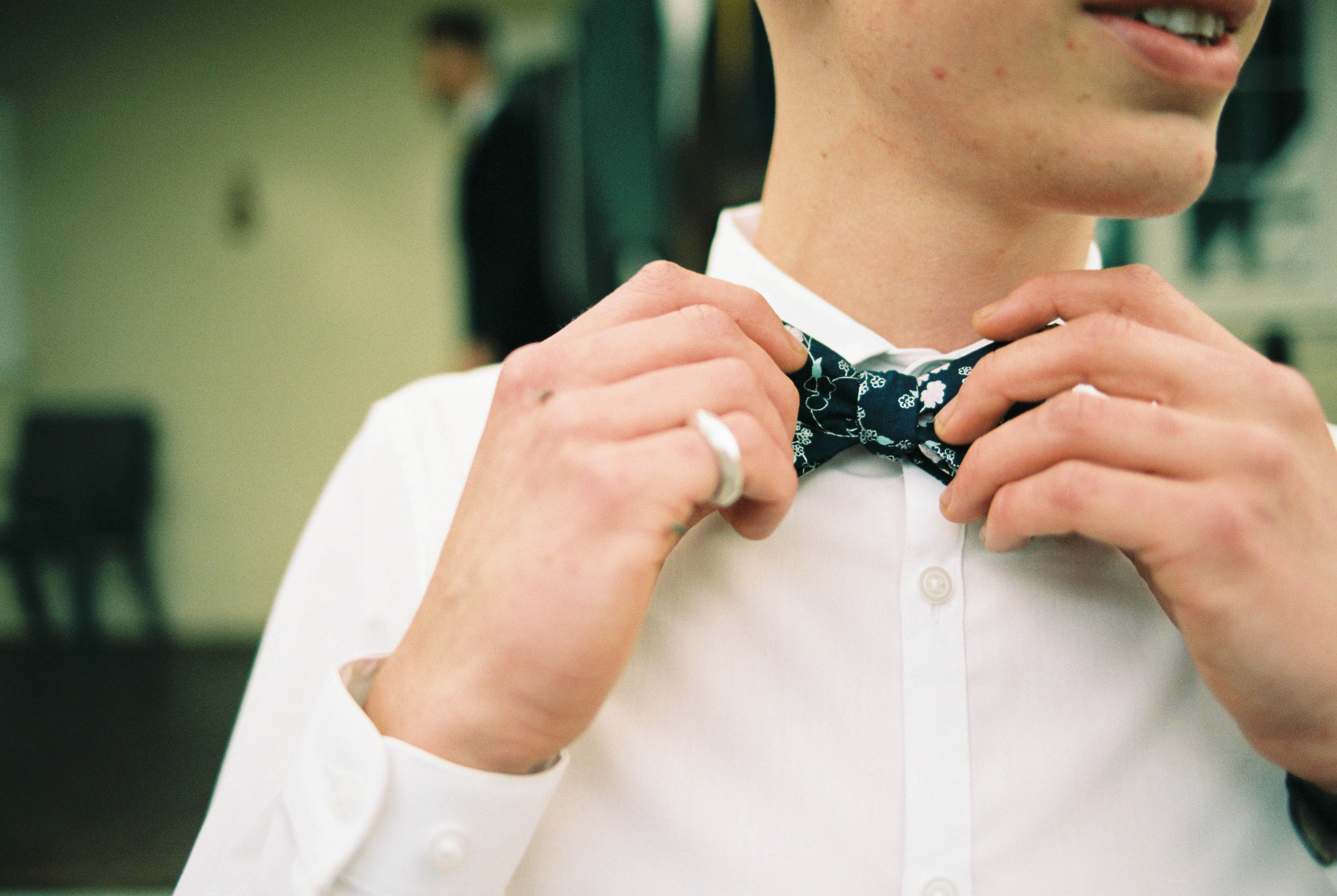 A close up film photo of a groomsman adjusting his hand-painted and handmade bowtie taken by Rhianna May Italy and Australia Destination Wedding Photographer