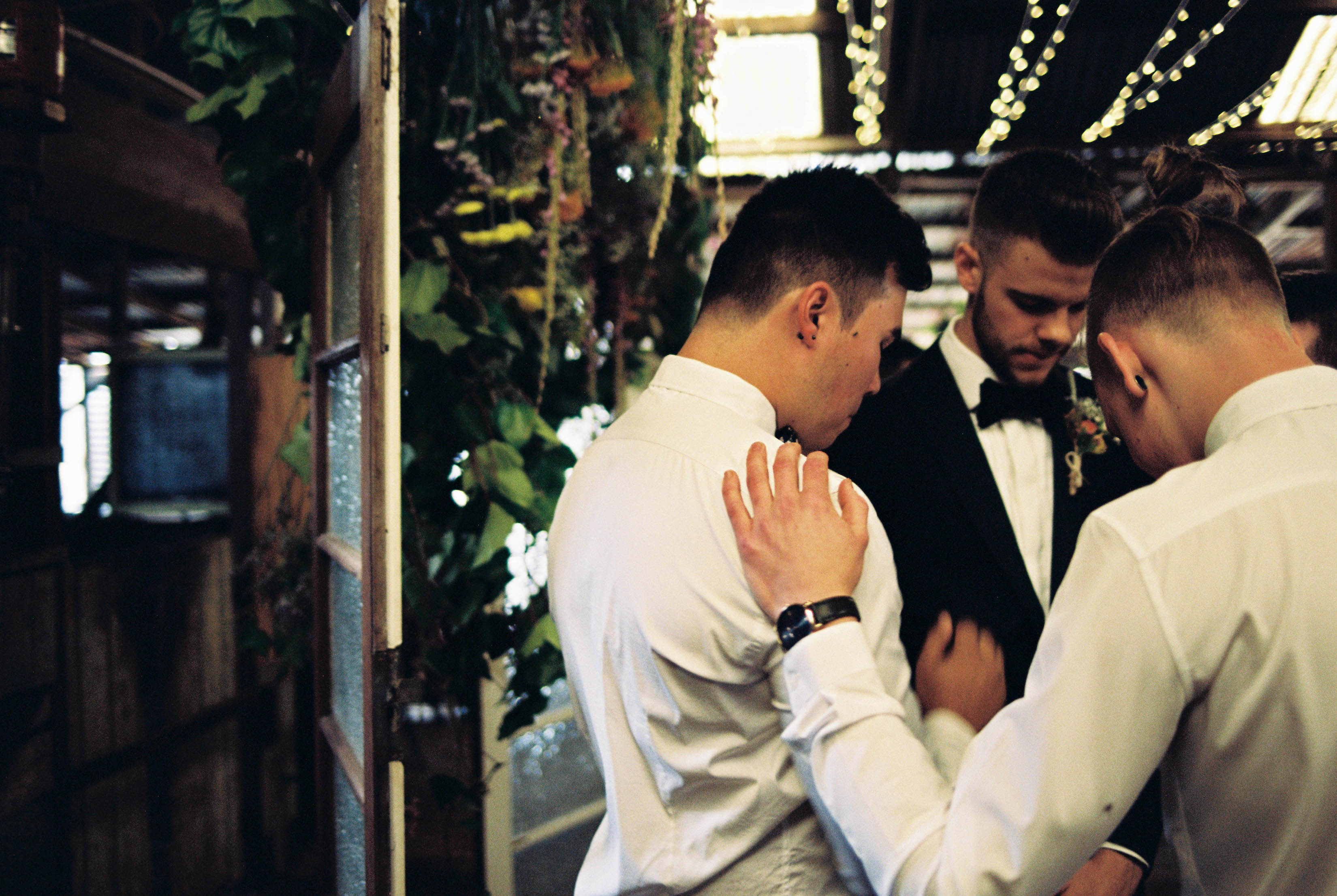 The groom and his groomsmen praying before the wedding ceremony begins