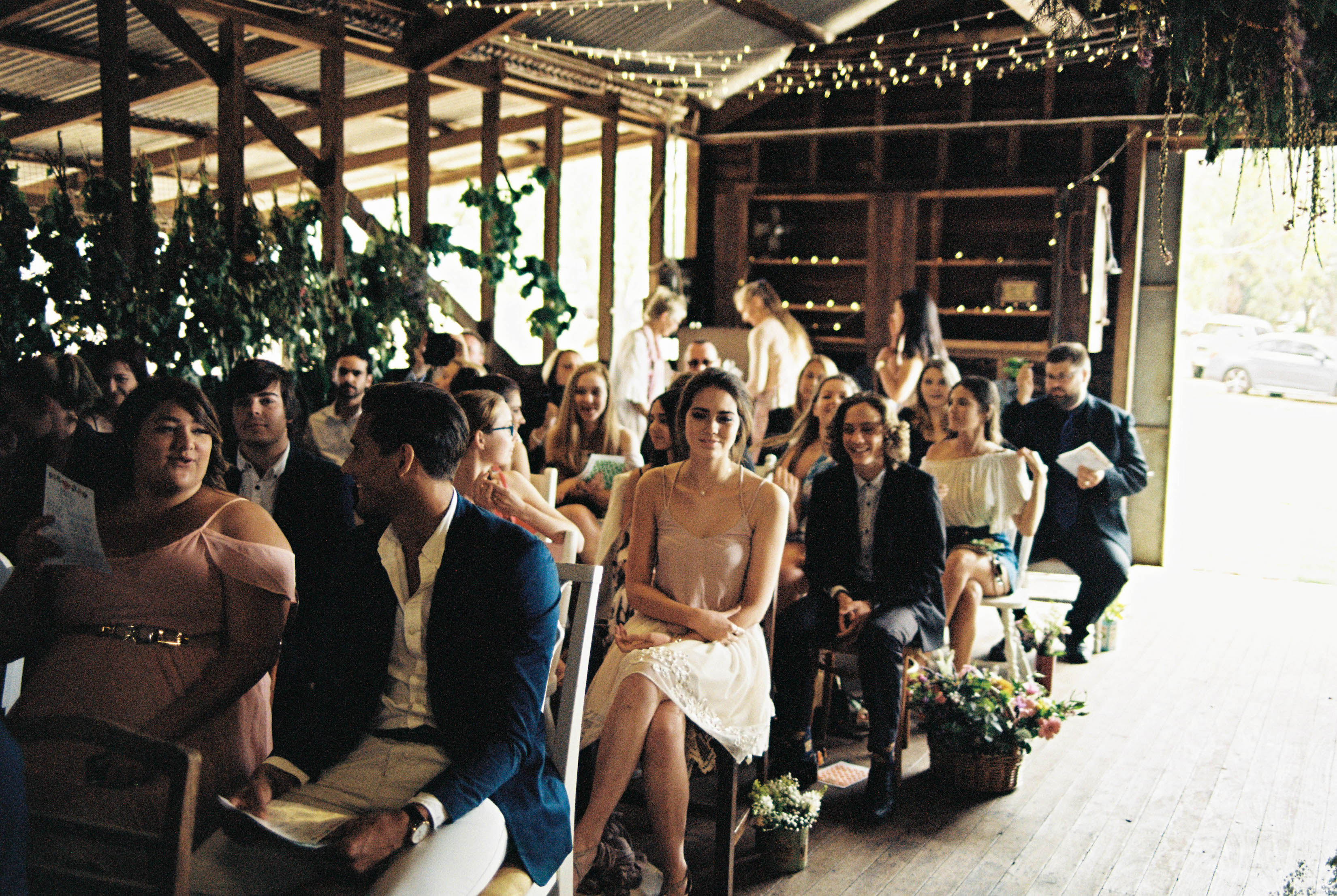 A photo of guests waiting for the wedding ceremony to start in a Shearing Shed in the South West