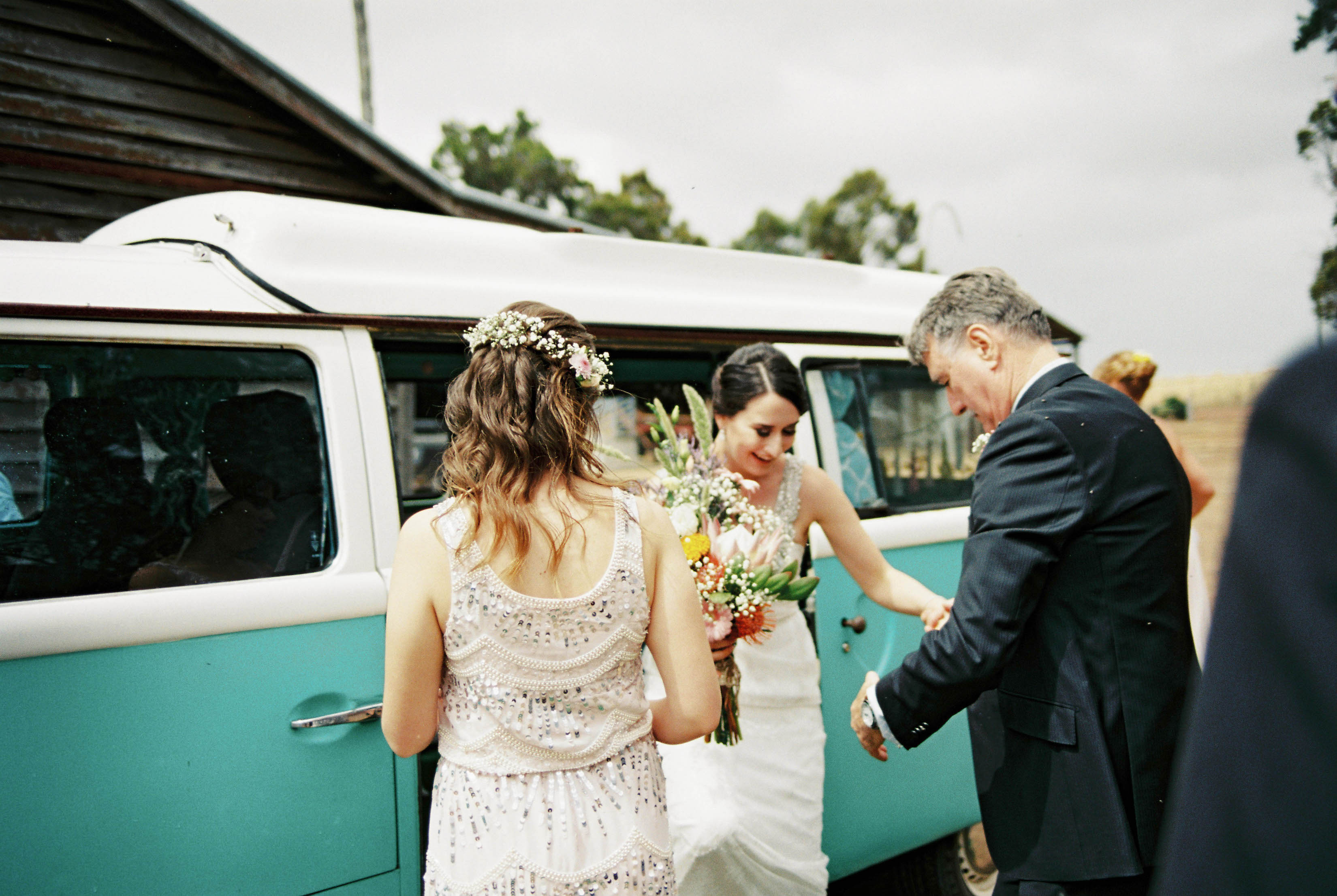 The bride stepping out of a vintage blue and white combi van photographed by Italian and Australian Wedding Photographer, Rhianna May