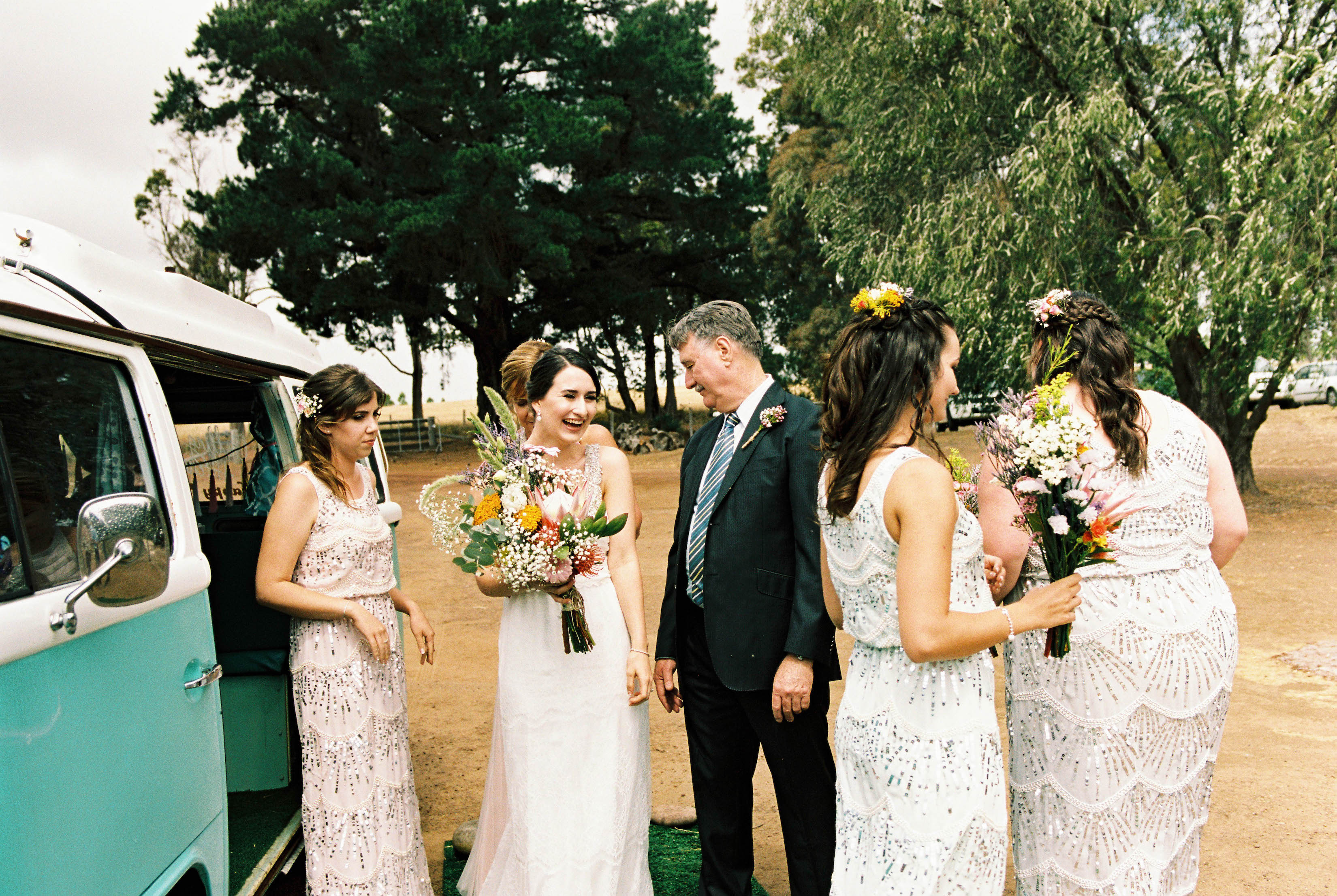 The bride greets her father after stepping out of the car on her wedding day at the family farm