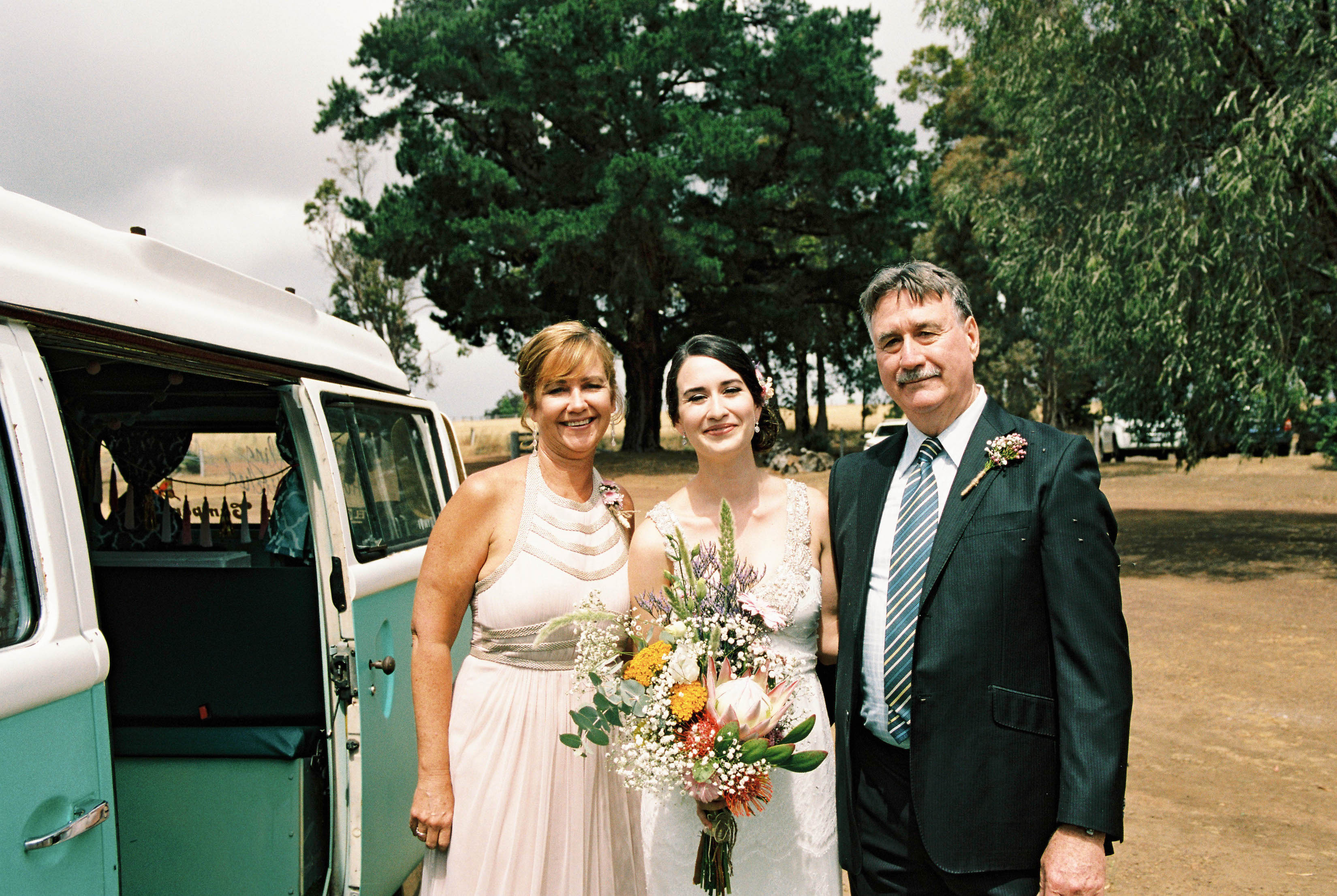 A portrait of the bride and her parents before the shearing shed wedding ceremony begins in Bridgetown, Australia
