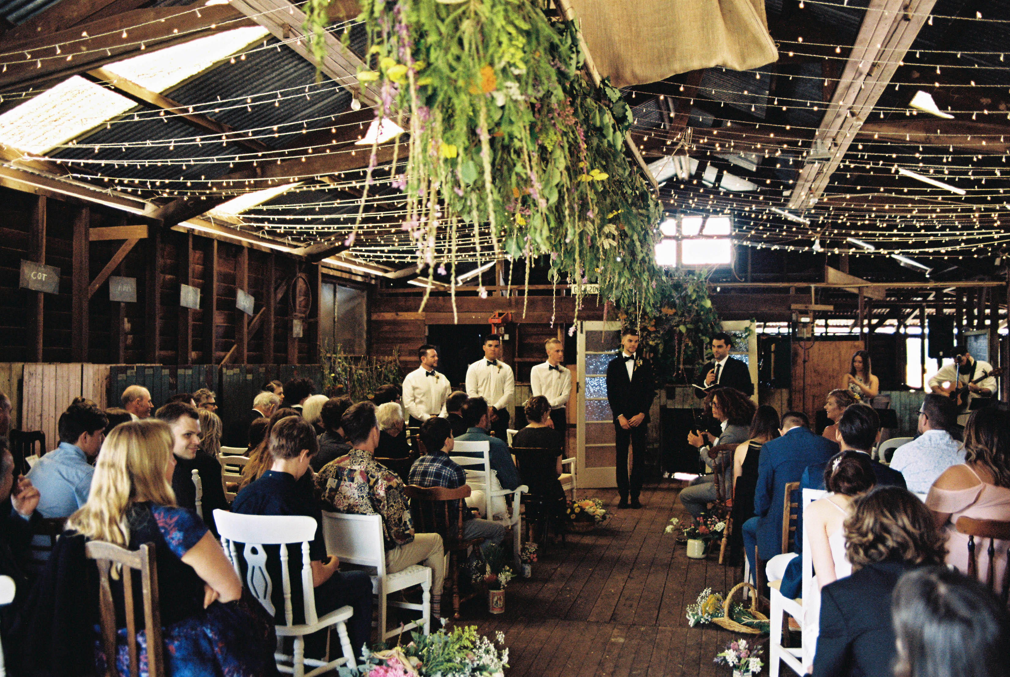 A wide shot of the wedding ceremony with fairy lights and a hanging flower installation in a shearing shed in the South West