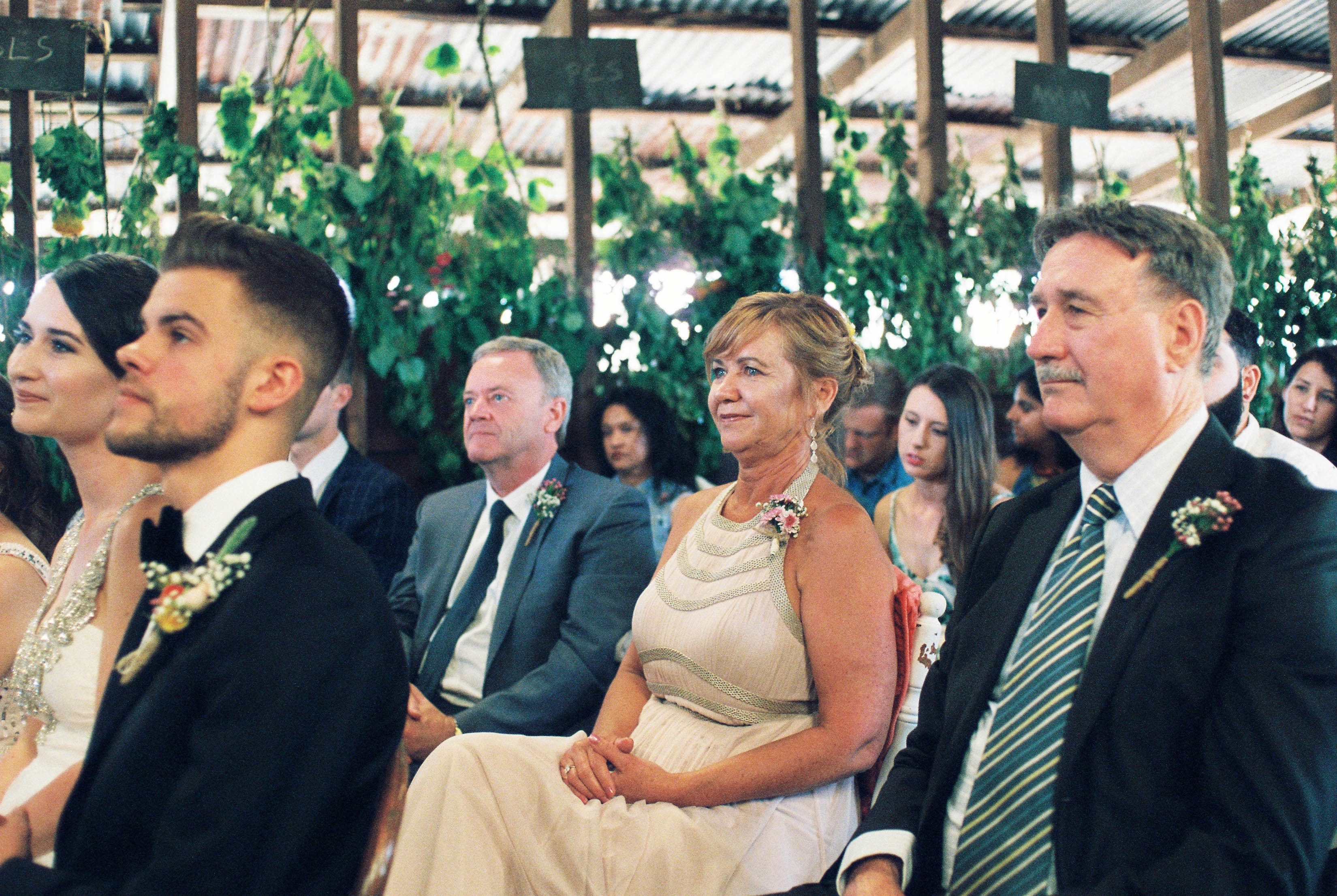 A photo of the bride's parents smiling during a shearing shed wedding ceremony