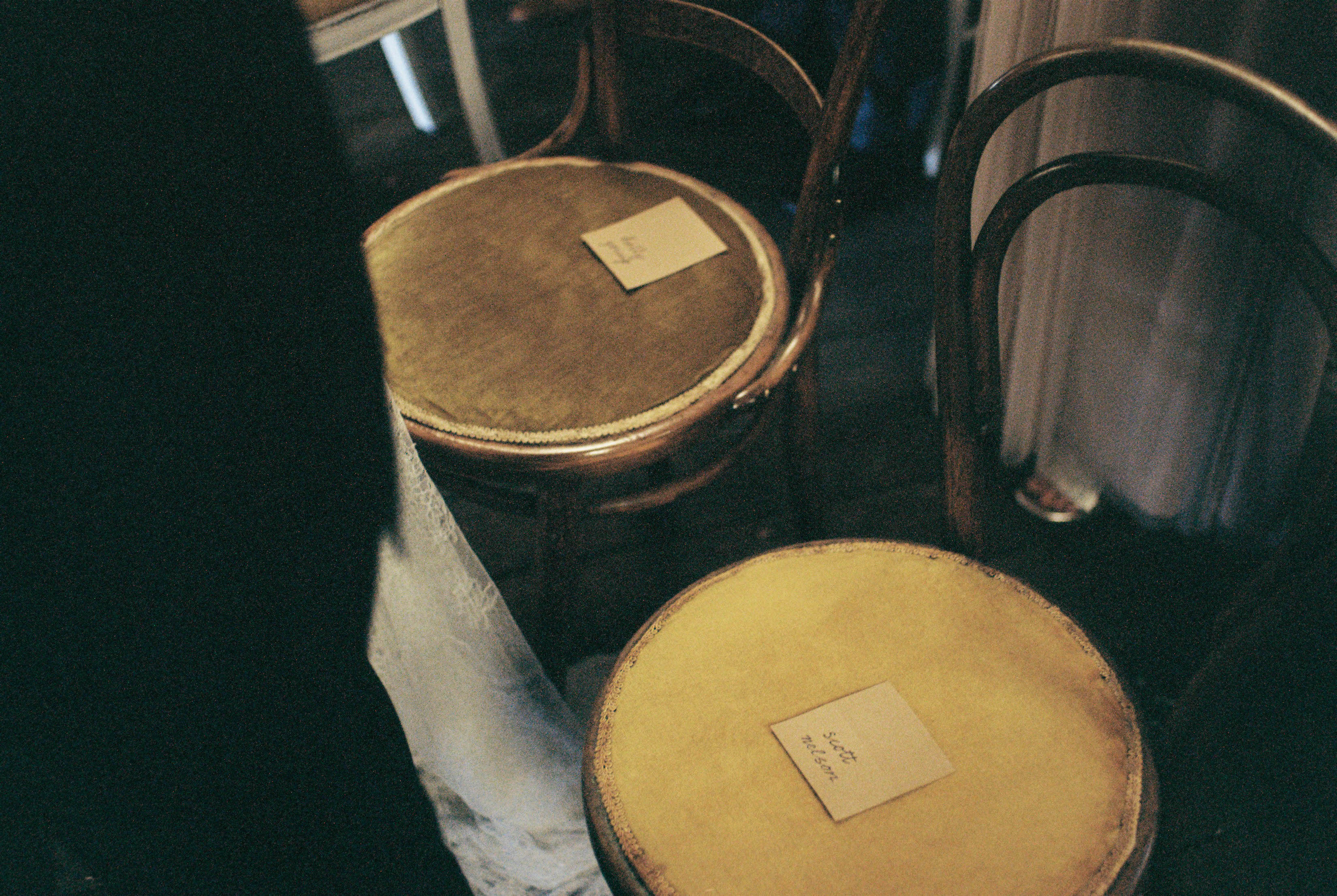 A detail photo of the groom's name tag on a vintage velvet chair during their Australian Country Wedding