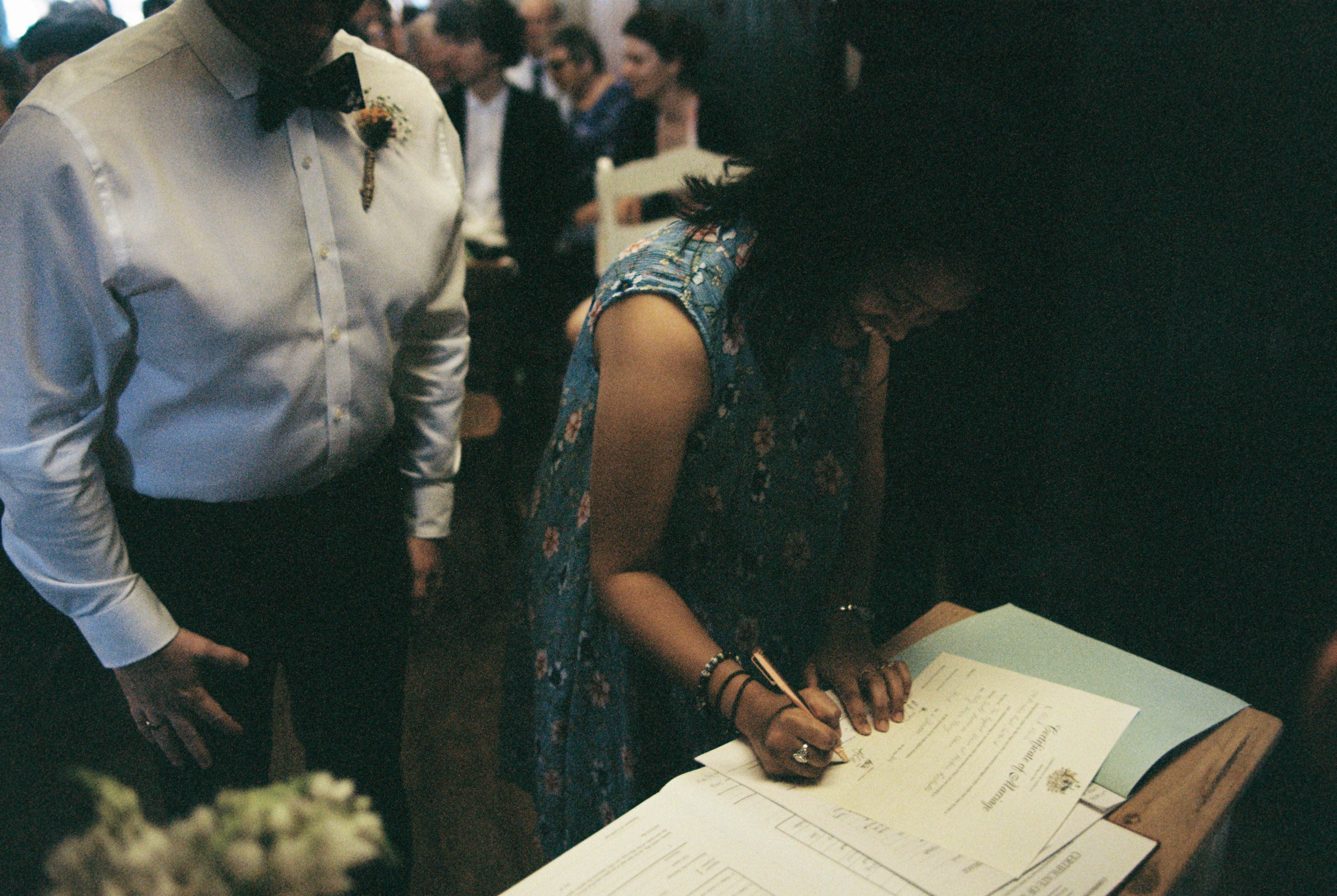 Two witnesses sign the wedding registry at a Bridgetown Wedding Ceremony