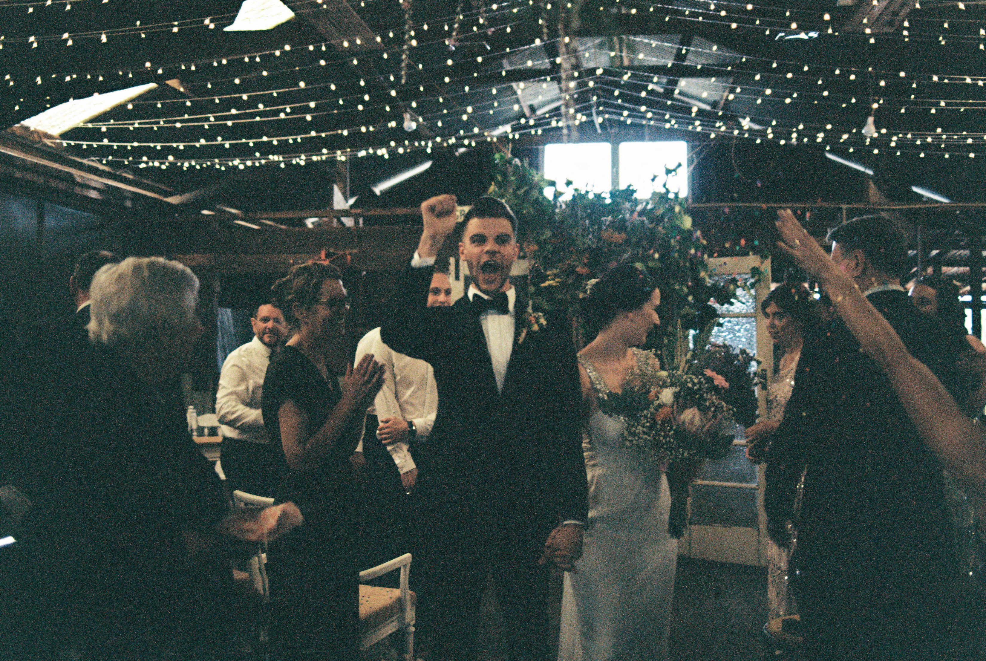 A photo of the groom cheering as he and the bride walk back down the aisle after their Bridgetown Wedding Ceremony