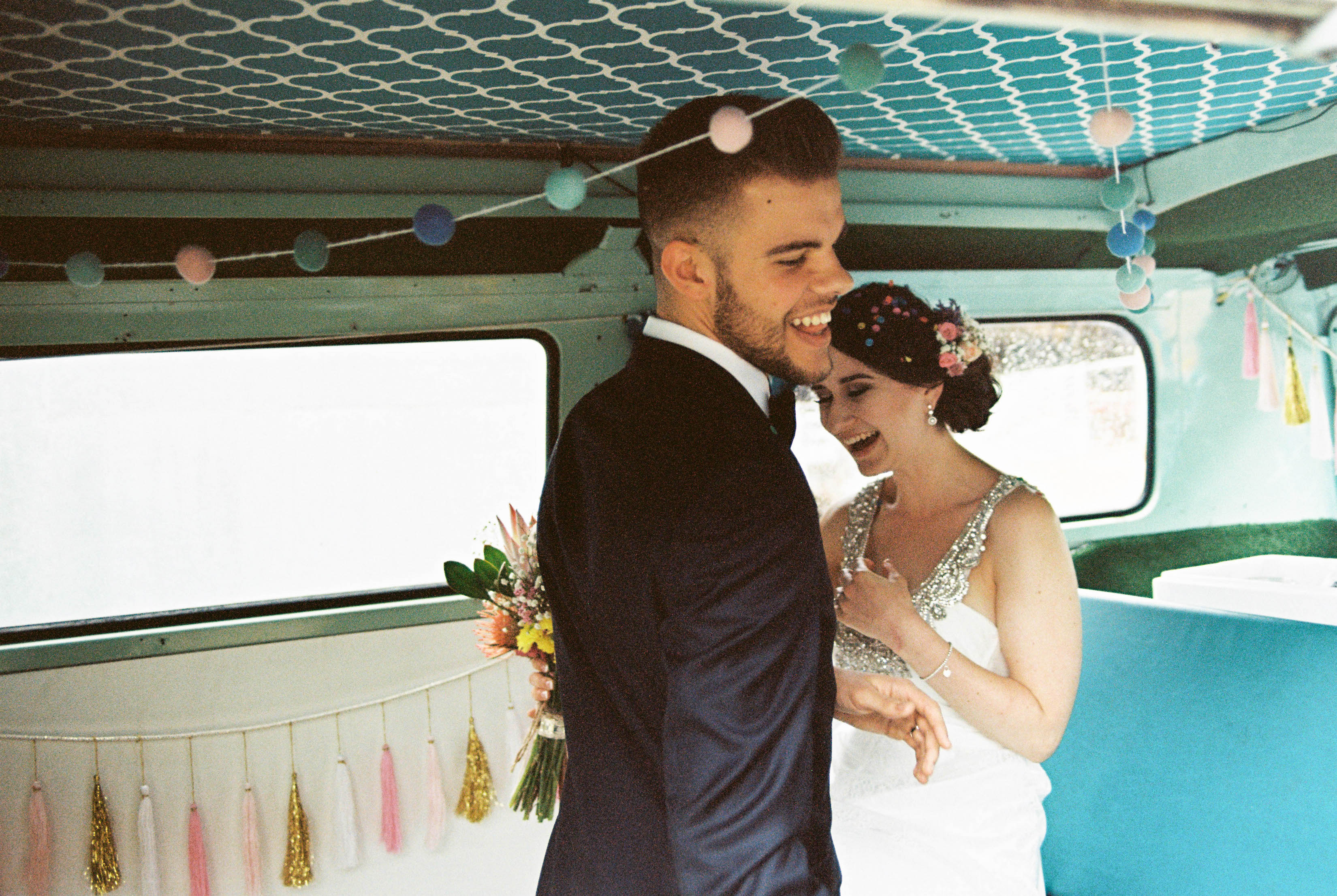 A photo of the bride & groom laughing together in a vintage Combi Van after their Bridgetown wedding