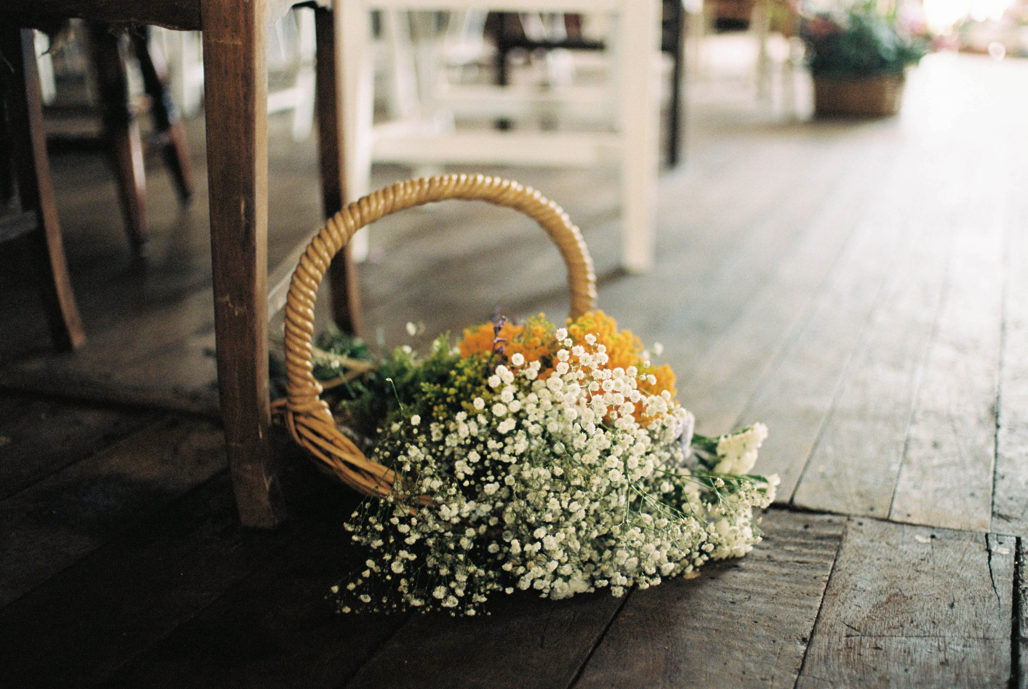 A photo of a basket of flowers decorating a Shearing Shed in Bridgetown for a wedding ceremony taken by Rhianna May Destination Wedding Photography