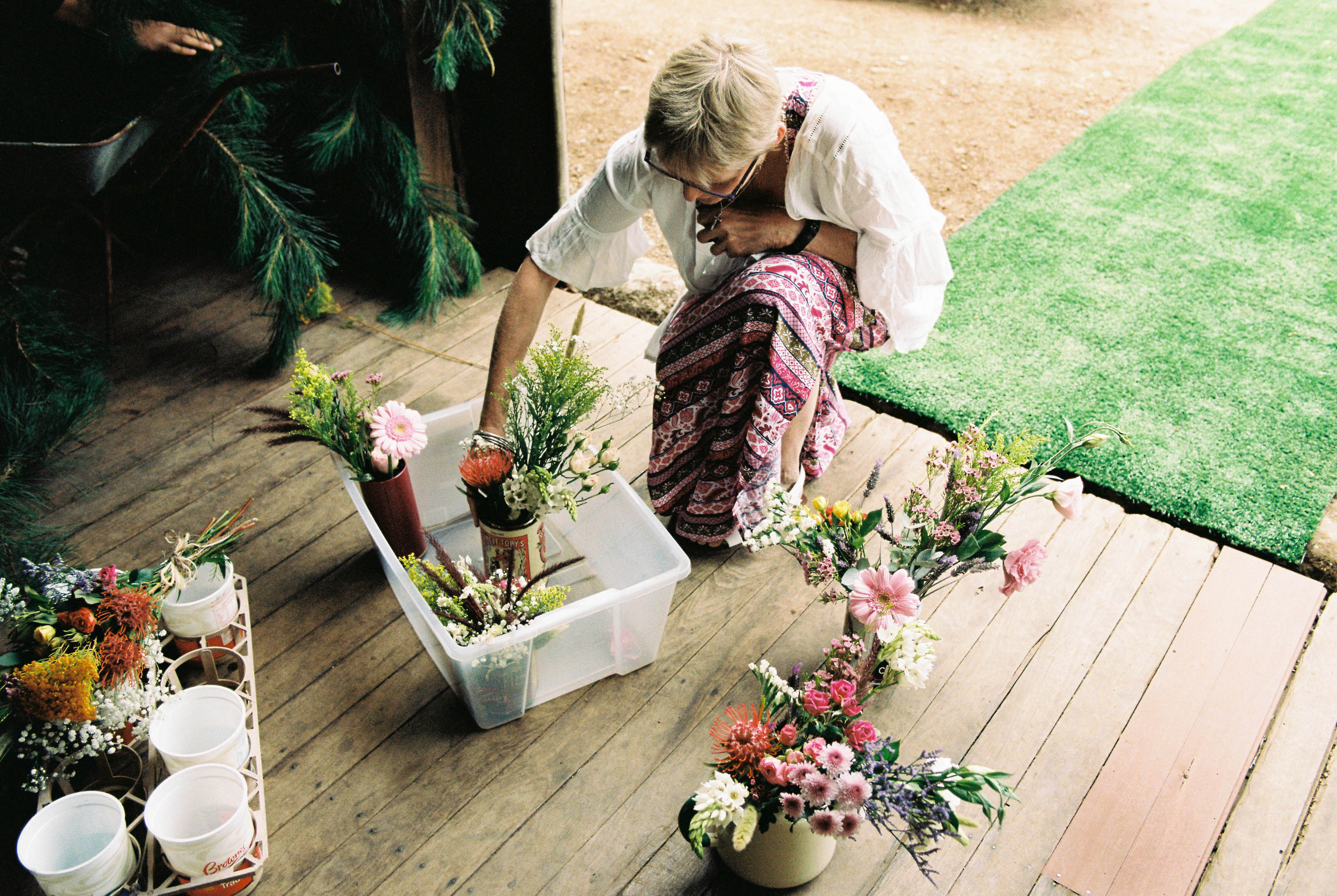 A photo of a stylist putting together flower decorations for a wedding in a shearing shed in Bridgetown