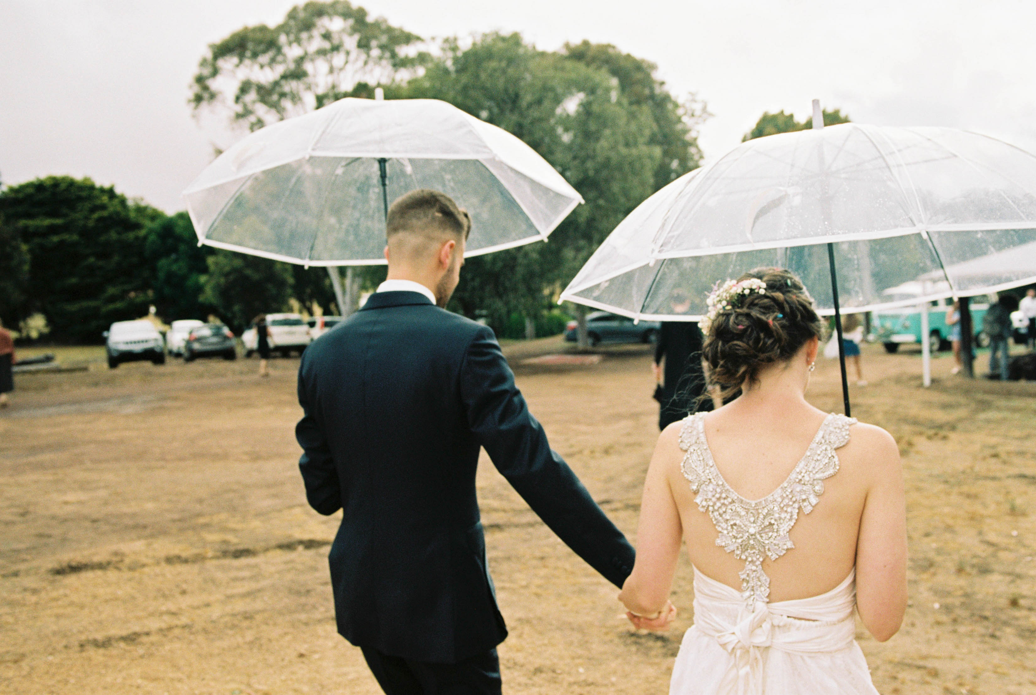 A photo of the bride & groom walking in the rain after their family farm portrait session