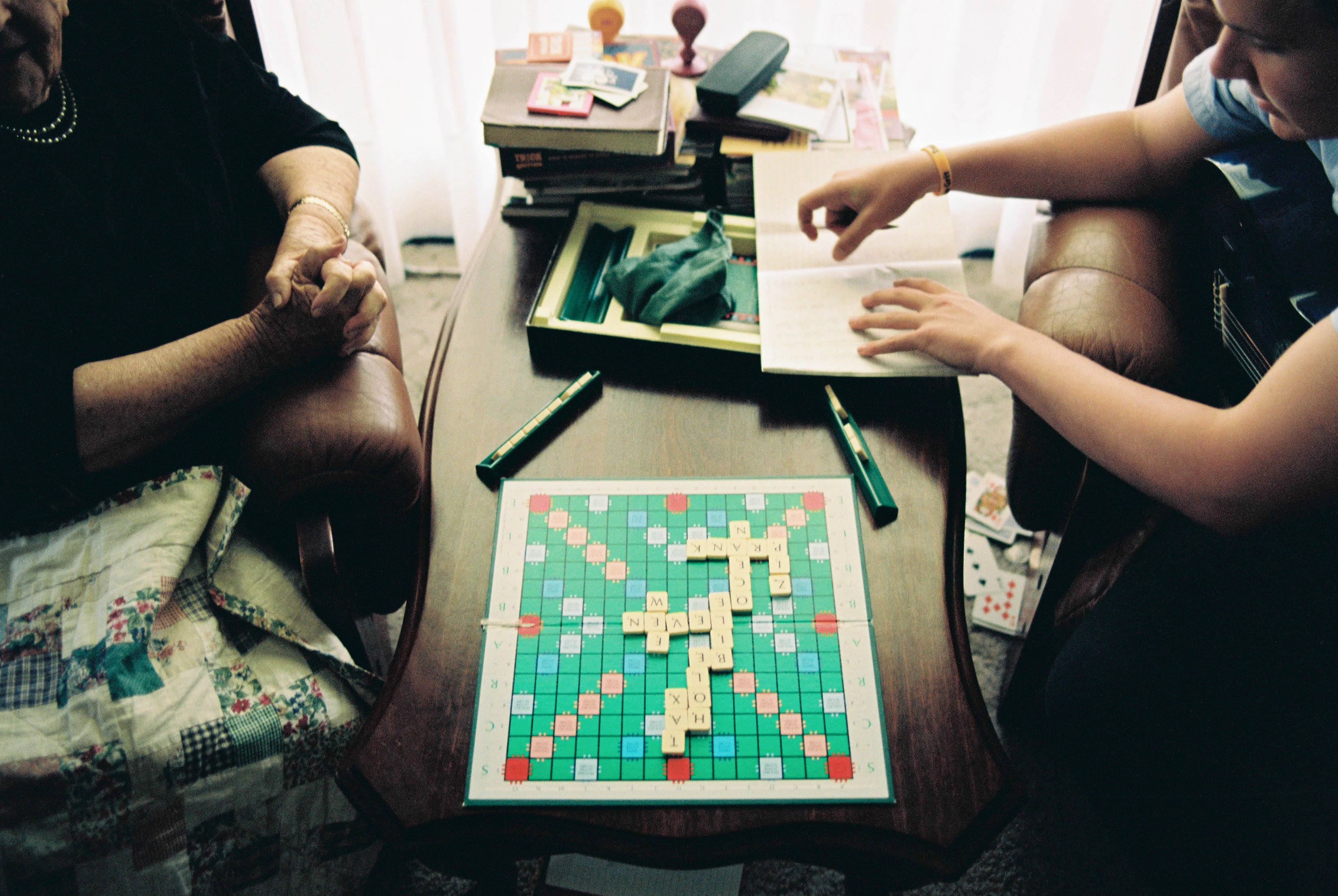Documentary wedding photography of the groom's grandma and cousin playing scrabble