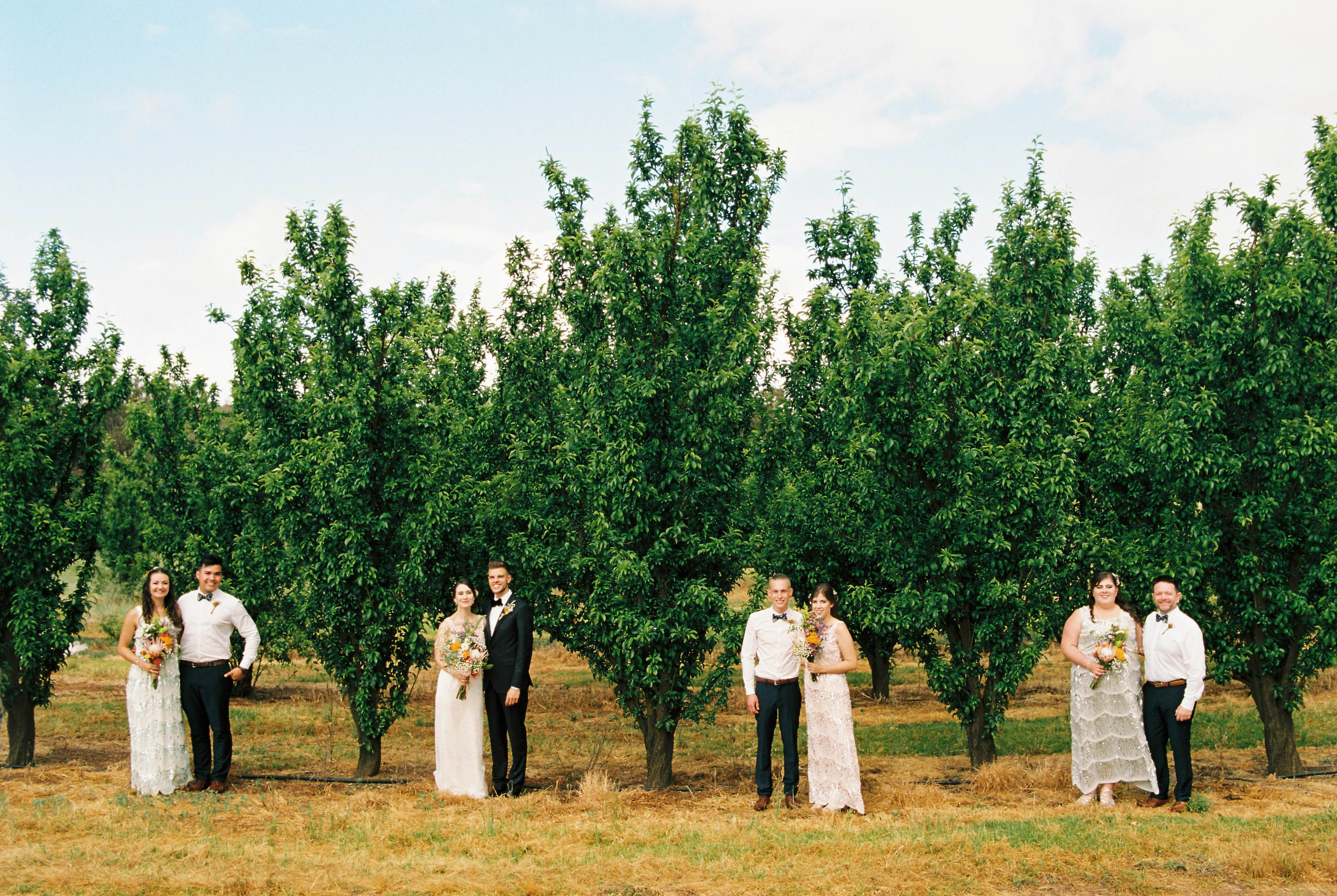 Perth Wedding Photography of a bridal party standing amongst the orchard on the family farm